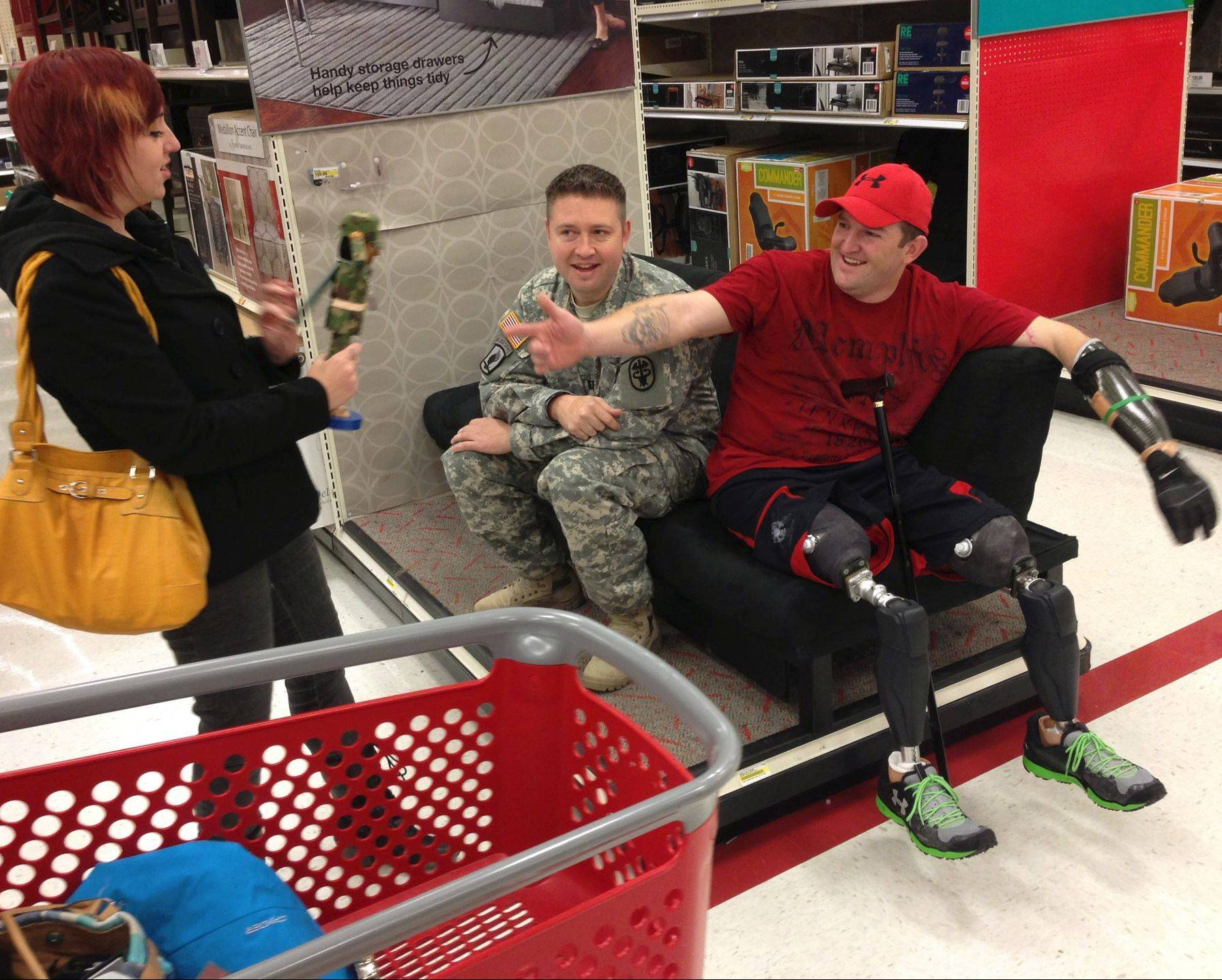 In a Target store, Captain Erik S. Johnson, center, and Sergeant Monte Bernardo and Bernardo's sister, Stella Shafer, joke about a nutcracker doll dressed in military fatigues who happens to be missing one arm.