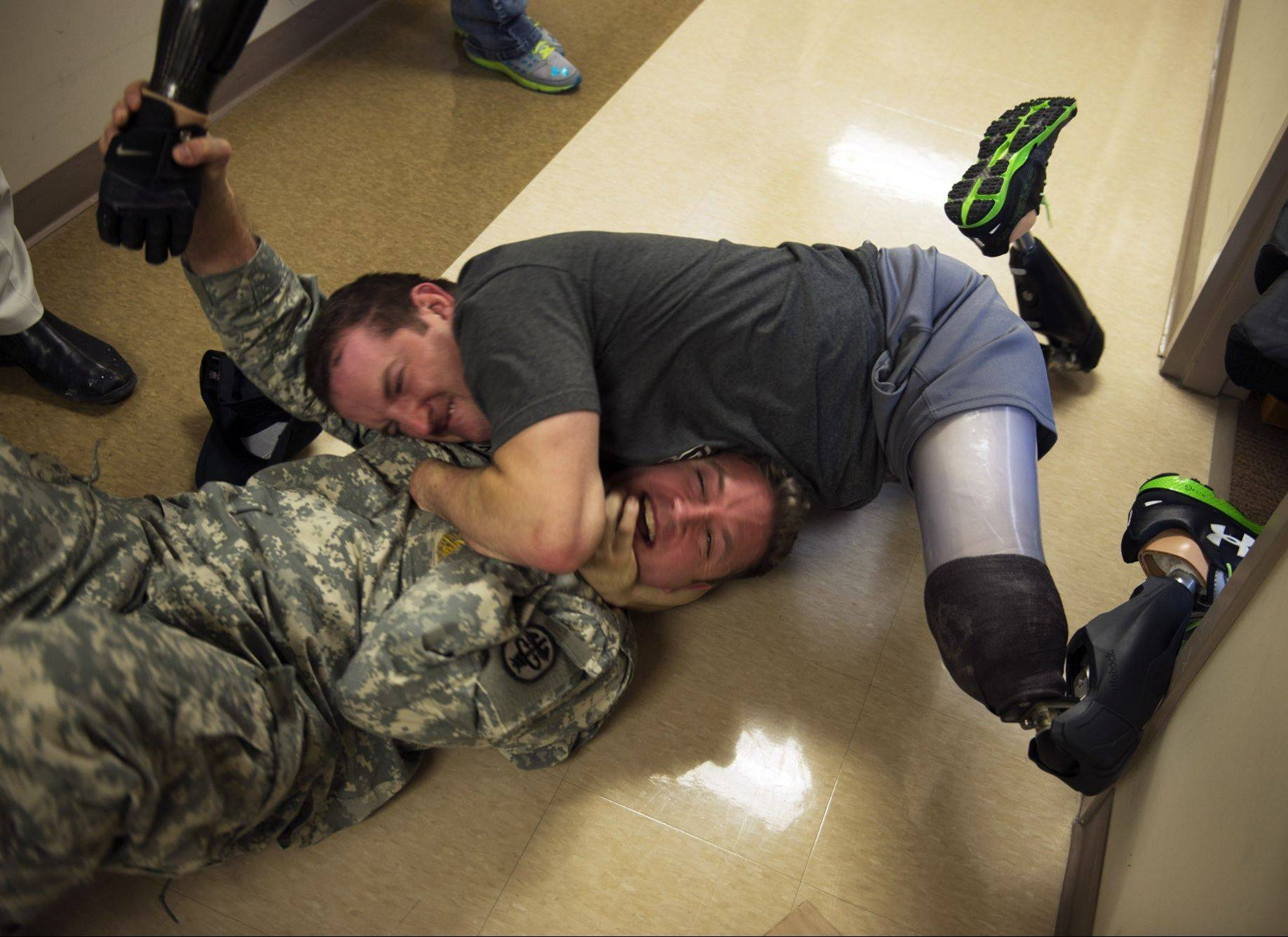 Army occupational therapist Captain Erik S. Johnson, left, and Sergeant Monte Bernardo, who was critically injured by an IED in Afghanistan, wrestle each other. The two men have become good friends during the long months of rehabilitation.