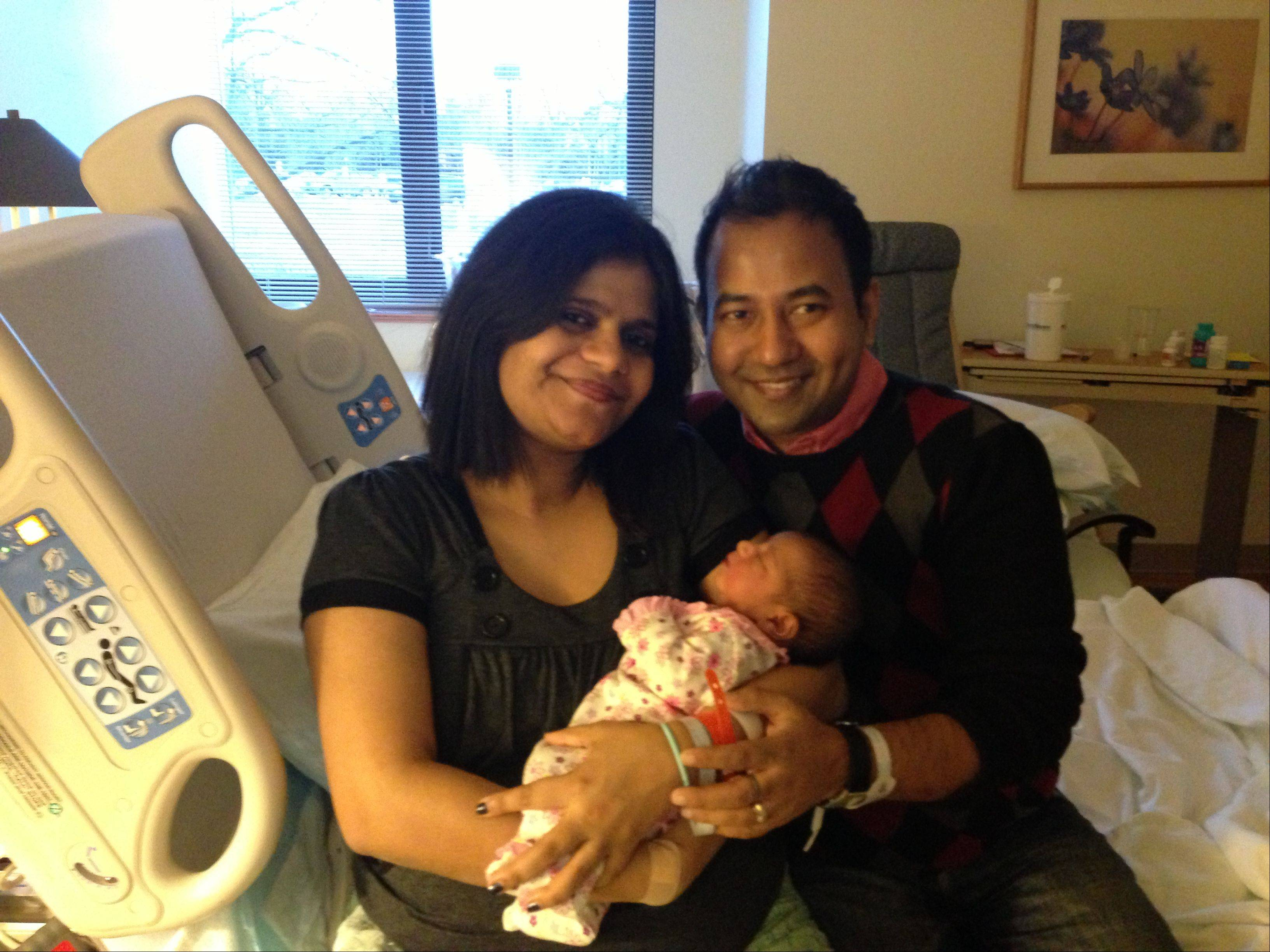 Aindrila Gupta holds her daughter, Naija Niyogi, as dad, Shiladitya Niyogi lends support. The couple's first child was born at 12:39 a.m. at NorthShore Highland Park Hospital, the first of the new year in Lake County.