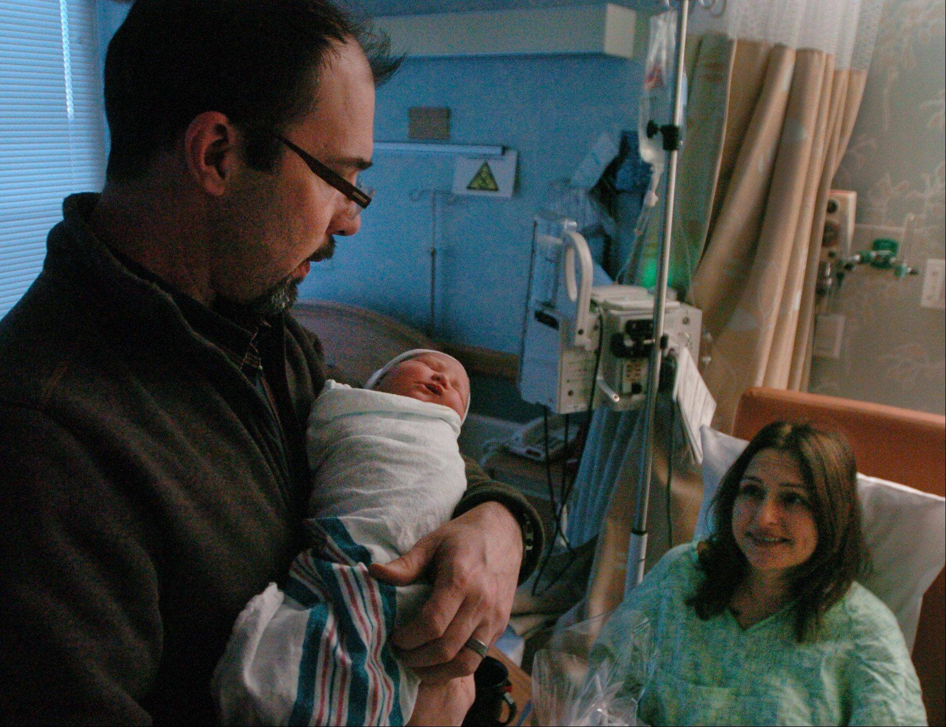 Hope Labbe, born at 12:13 a.m. on New Year's Day, rests in the arms of her father, Sean Labbe, as her mom, Fidan looks on at St. Alexius Medical Center in Hoffman Estates.