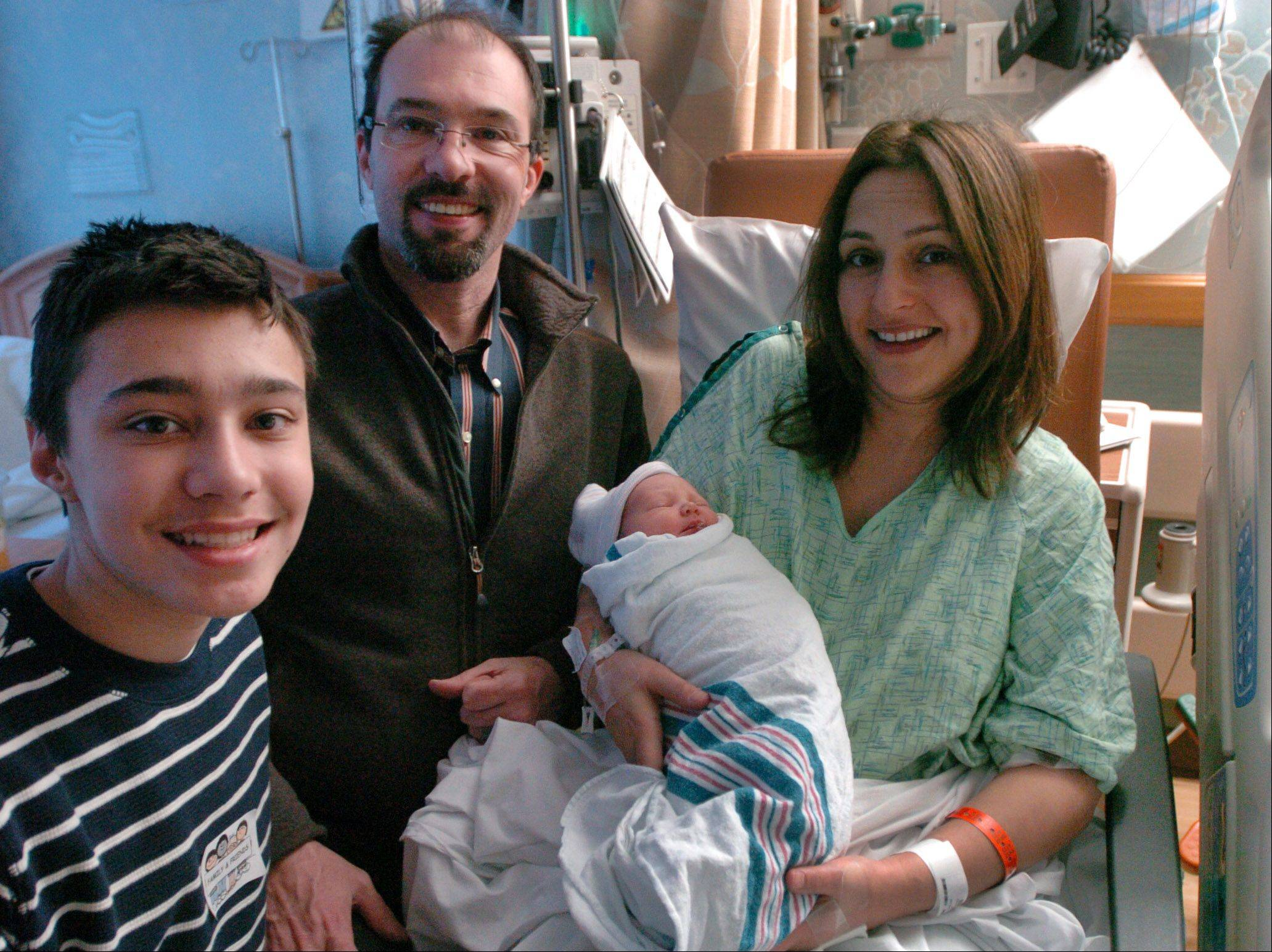 Hope Labbe, the first baby born on New Year's Day in Northwest Cook County, rests with mother and father Fidan and Sean Labbe, along with big brother, Brendan, at St. Alexius Medical Center in Hoffman Estates.