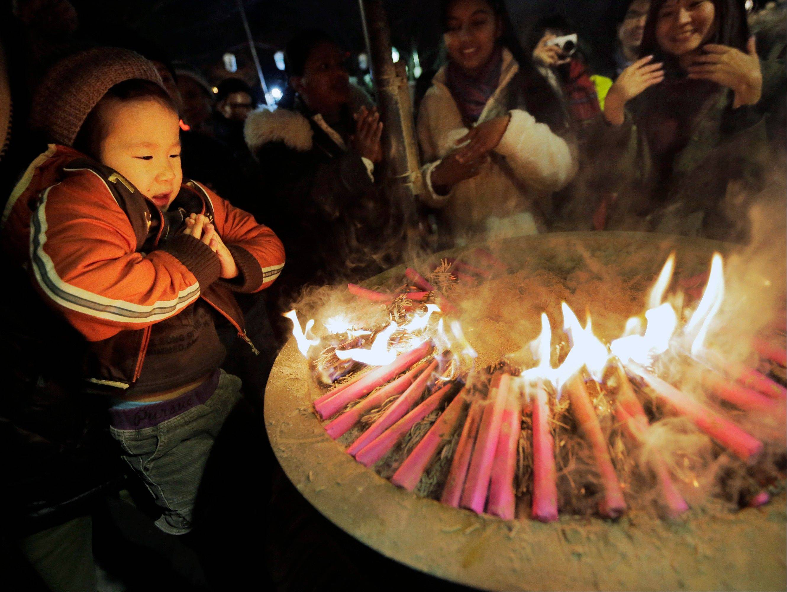 A boy prays around a fire believed to invoke divine help during their first visit of the year to the Zojoji Buddhist temple in Tokyo, Monday, Dec. 31, 2012.