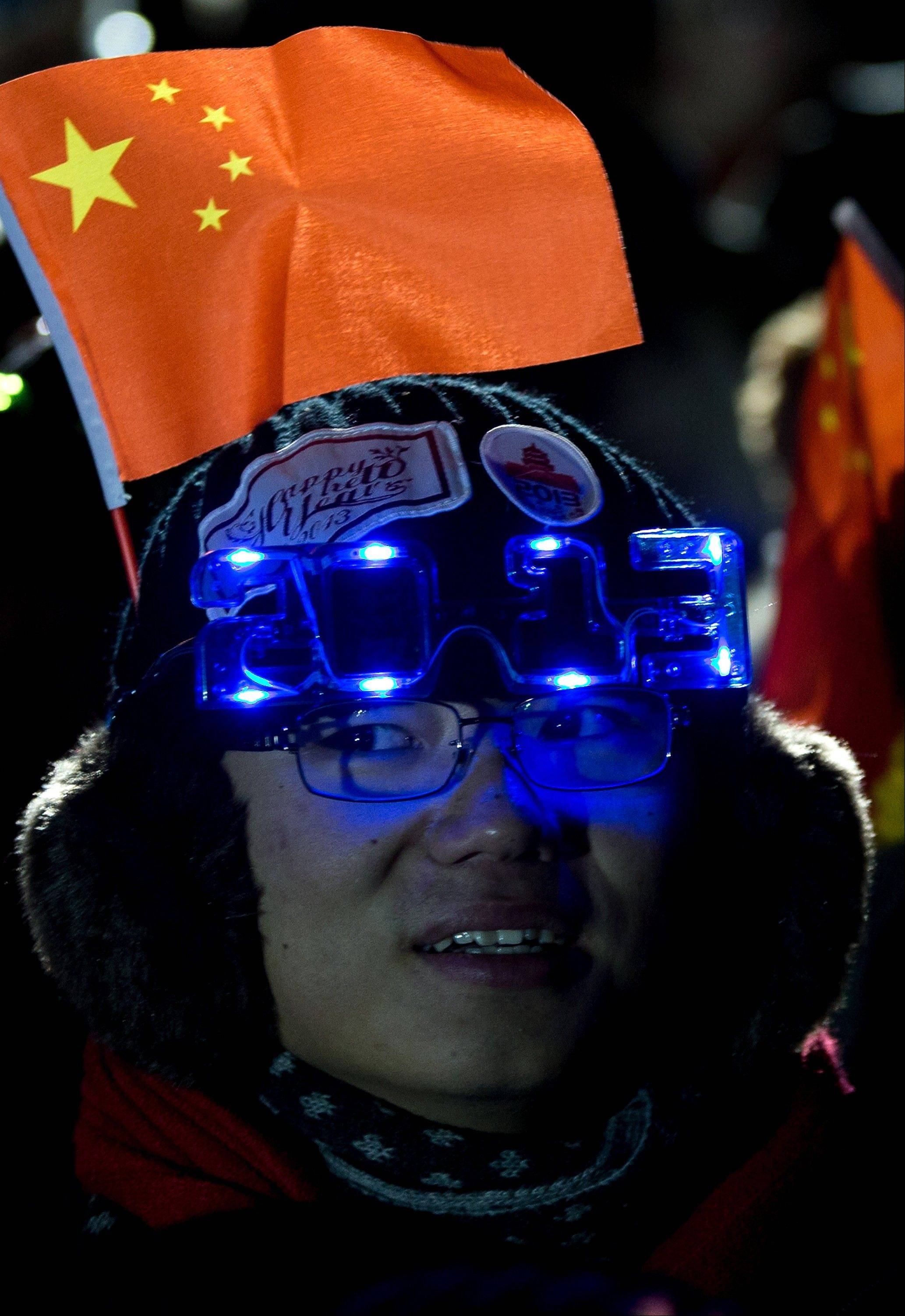 A Chinese man wears 2013-style glasses and a national flag as he celebrates the new year during a count-down event at the Summer Palace in Beijing Tuesday, Jan. 1, 2013.