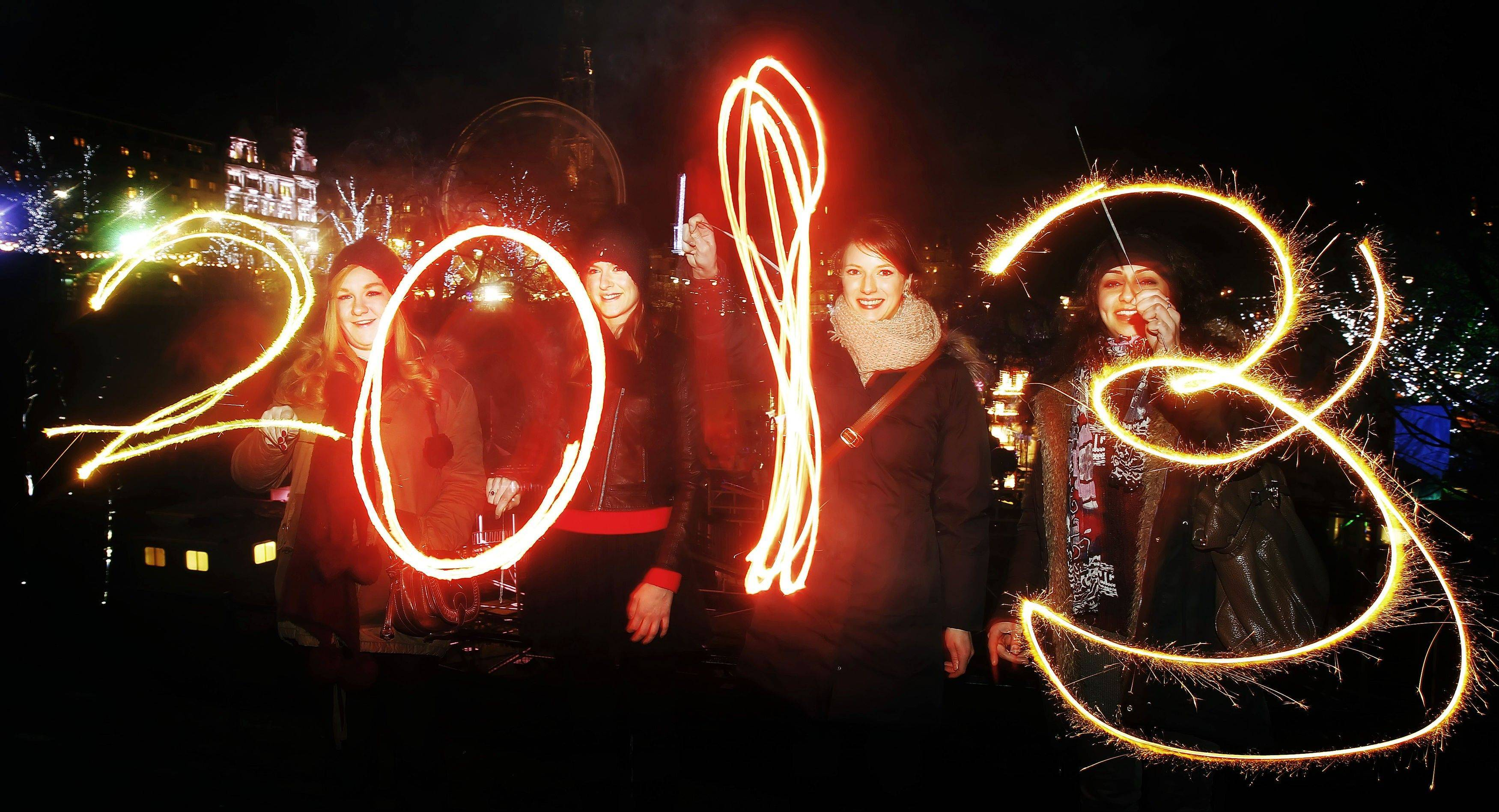 Katy Saunders, left, Alex Mueller, center left, Rebekka Frank and Arina Motamedi, right, play with sparklers ahead of welcoming in the new year during the 2013 Edinburgh Hogmanay celebrations, Scotland, Monday December 31, 2012.