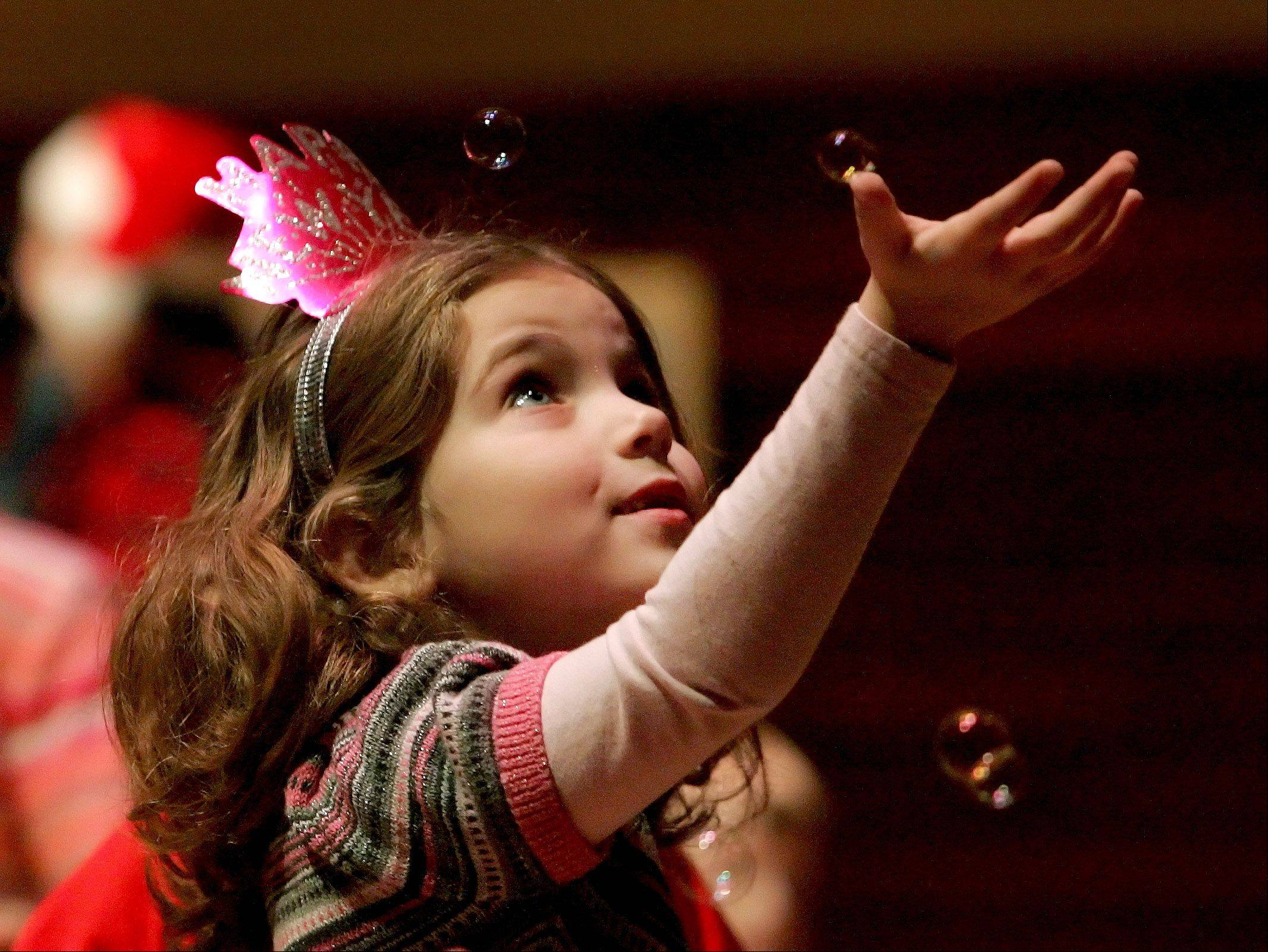 Katie Harley, 5, of Naperville, tries to catch a bubble as she celebrates at the DuPage Children's Museum's Bubble Bash Monday at Wentz Concert Hall in Naperville.