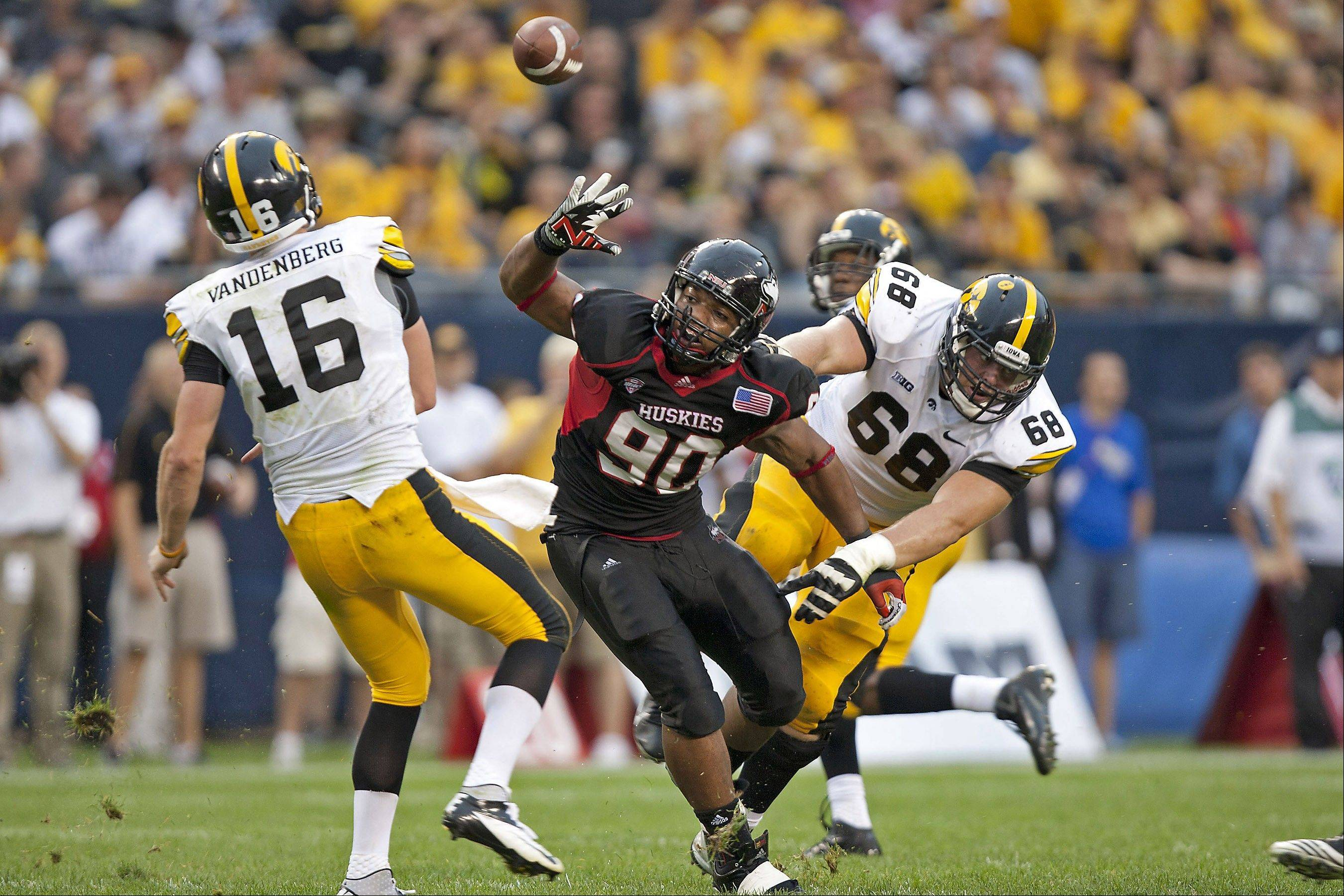 Northern Illinois defensive end Alan Baxter of Buffalo Grove applies pressure on Iowa's quarterback at Soldier Field.