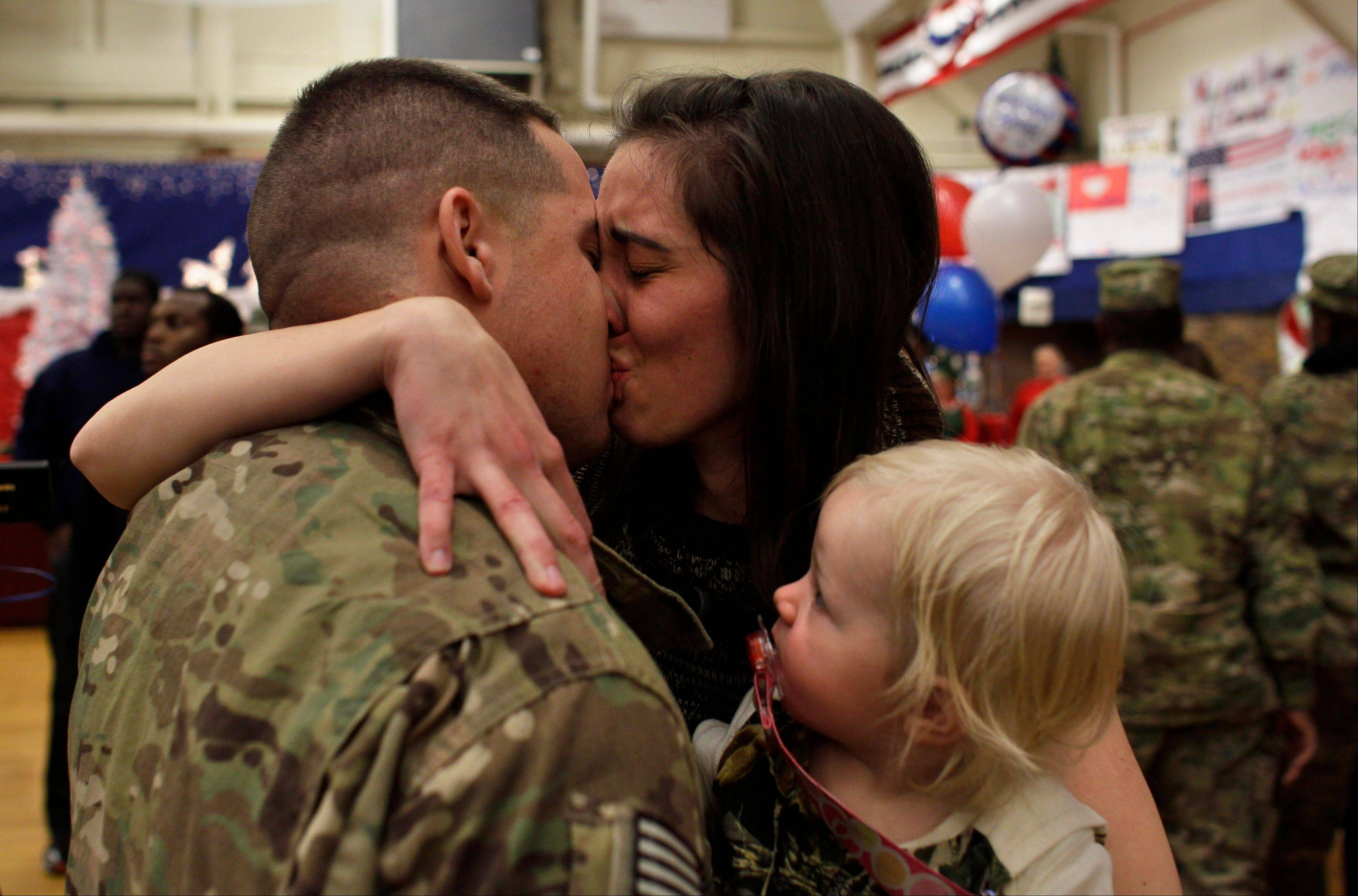U.S. Army 1st Lt. Aaron Dunn kisses his wife, Leanne, holding their baby Emma, age 14 months, as they reunite during an arrival ceremony for soldiers returning from a deployment in Afghanistan at Ft. Carson, in Colorado Springs, Colo.