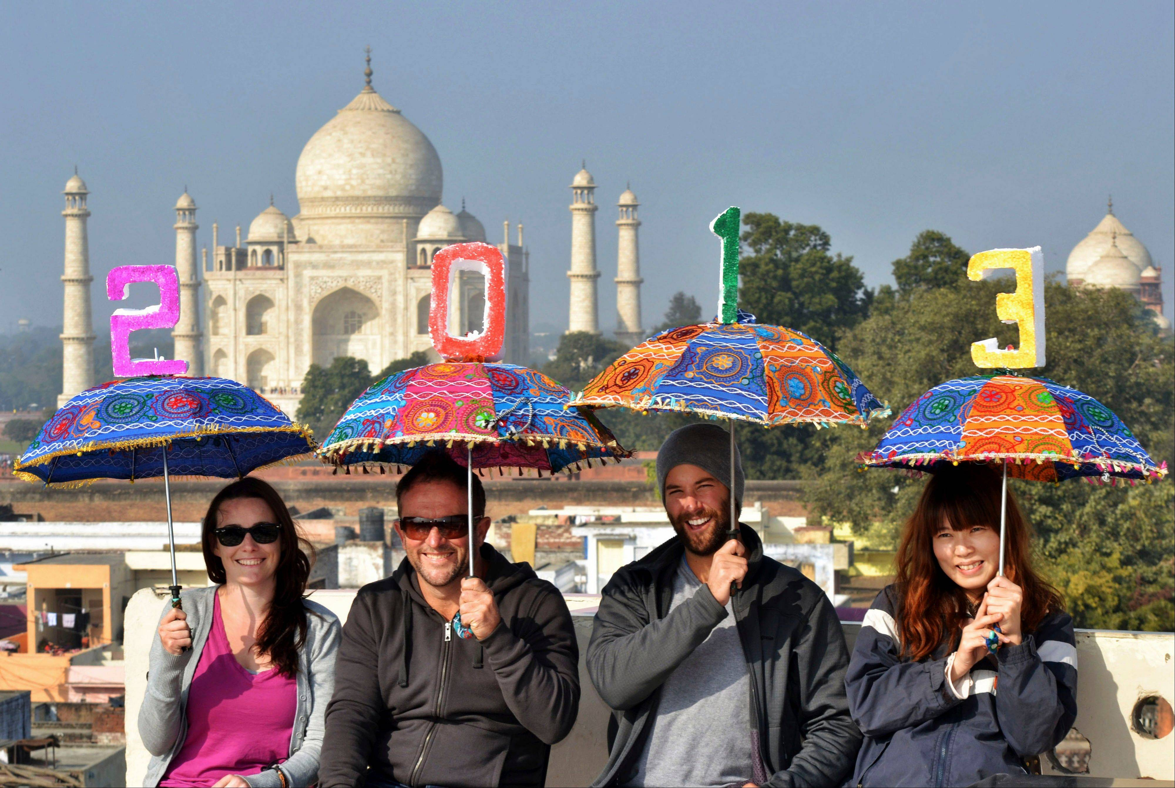 Tourists pose as they carry umbrellas with numbers to welcome the New Year 2013 on the terrace of a hotel in the backdrop of Taj Mahal in Agra, India, Monday.