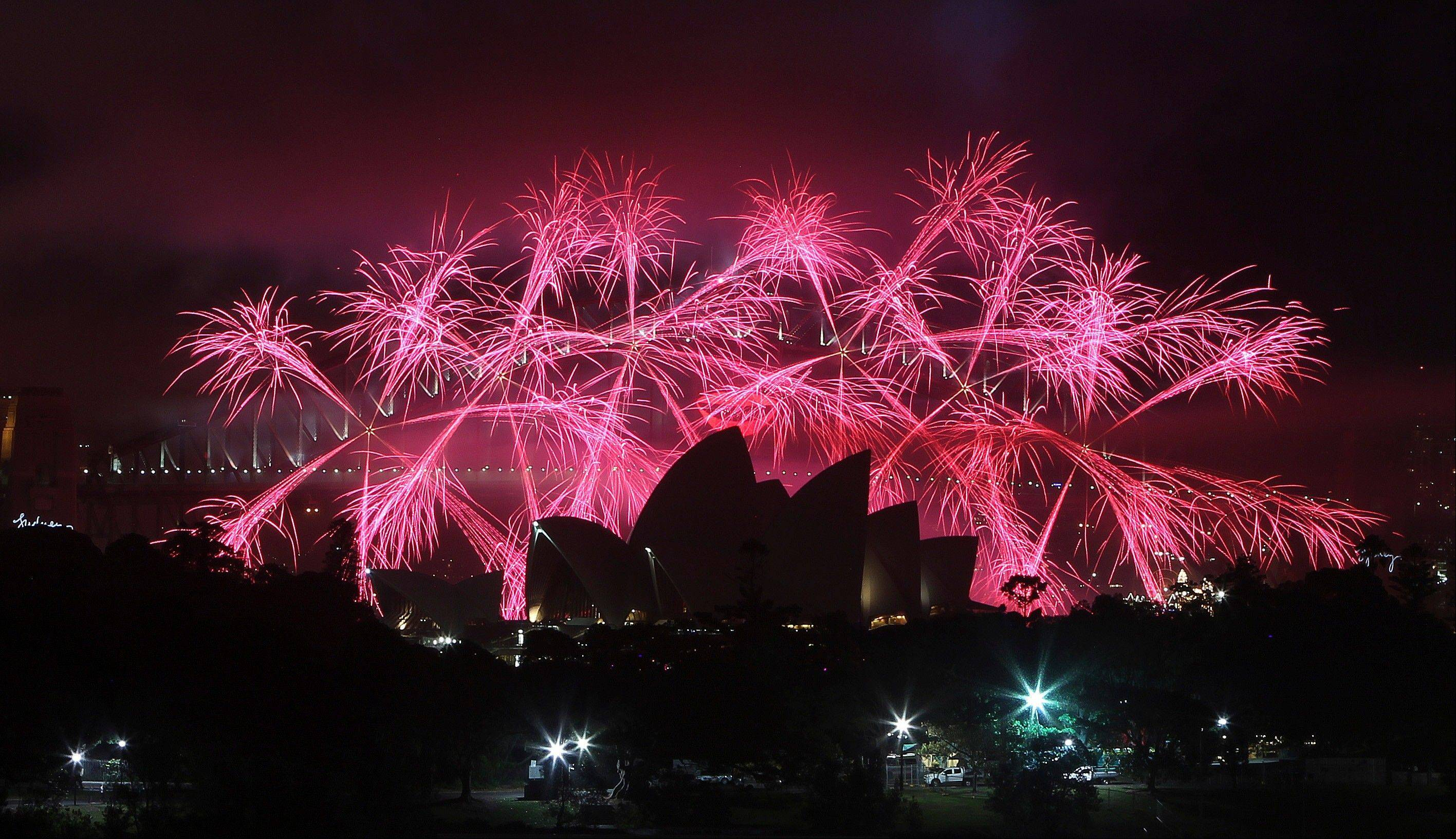 Fireworks explode behind the Opera House during the New Year celebrations in Sydney, Australia, Tuesday.