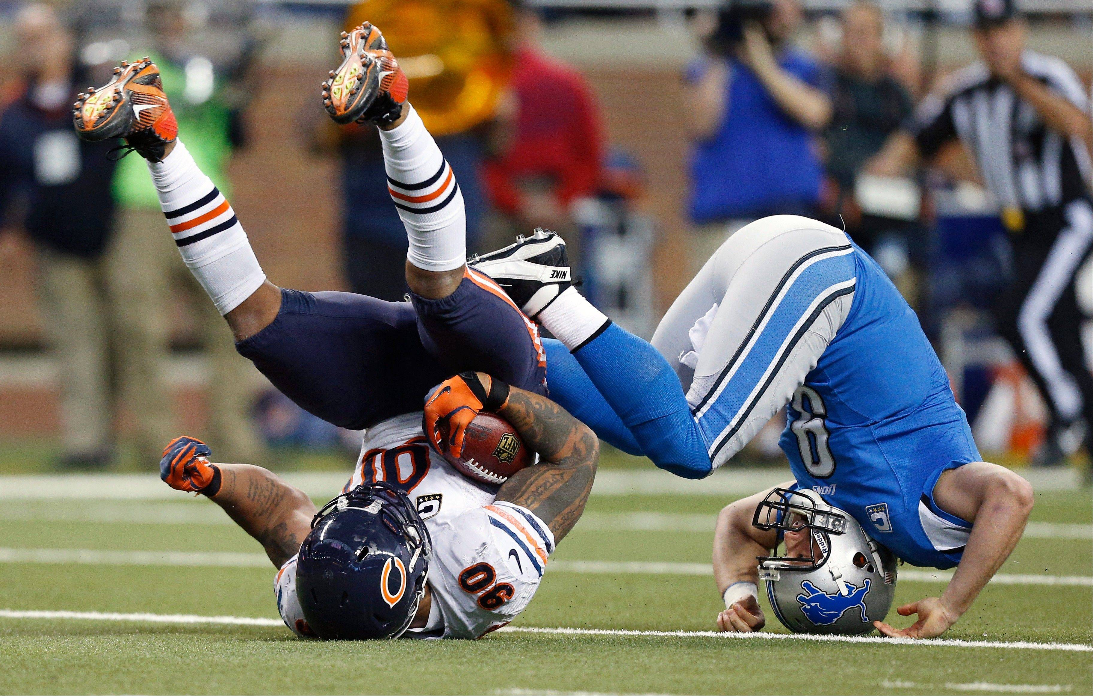 Chicago Bears defensive end Julius Peppers (90) recovers a loose ball and is stopped by Detroit Lions quarterback Matthew Stafford (9) during the second quarter Sunday at Ford Field in Detroit. The Bears would ultimately beat the Lions but lose out on the playoffs after the Minneosta Vikings beat the Green Bay Packers.