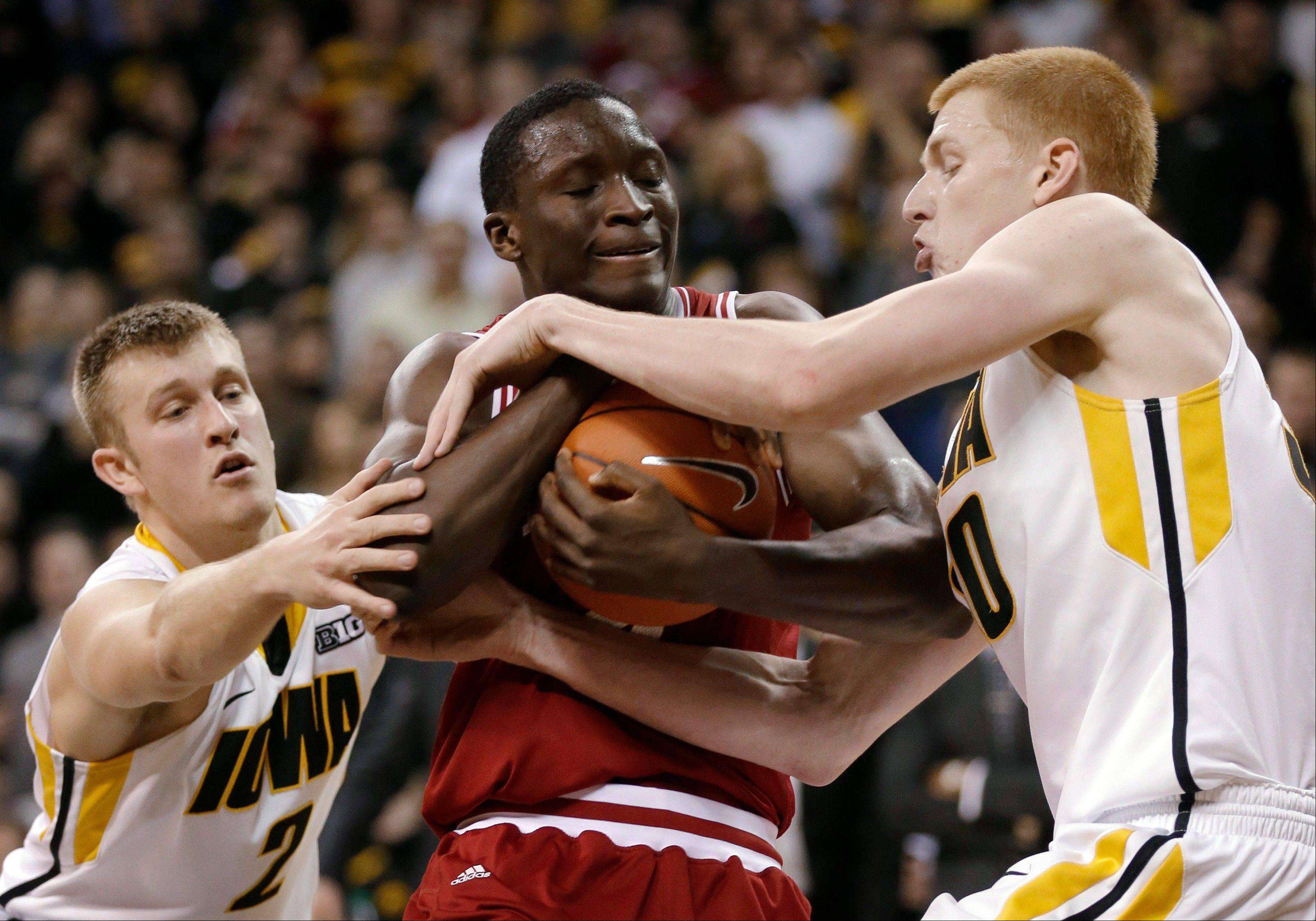 Indiana guard Victor Oladipo, center, grabs a rebound between Iowa defenders Josh Oglesby, left, and Aaron White during the second half Monday in Iowa City, Iowa.