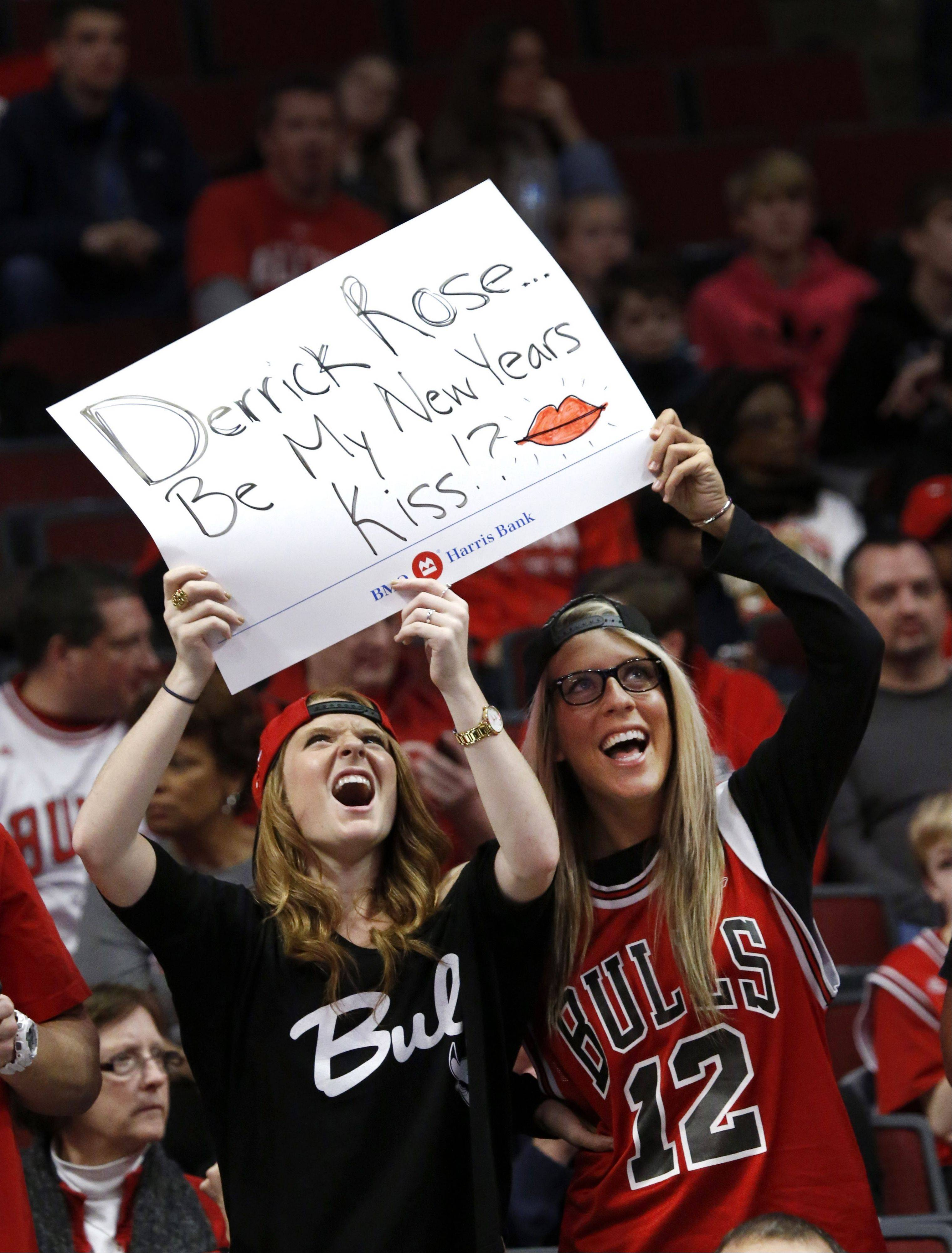 Two Chicago Bulls fans hold up a sign and watch themselves on the big screen before an NBA basketball between the Bulls and the Charlotte Bobcats on Monday, Dec. 31, 2012, in Chicago. The Bobcats won 91-81.