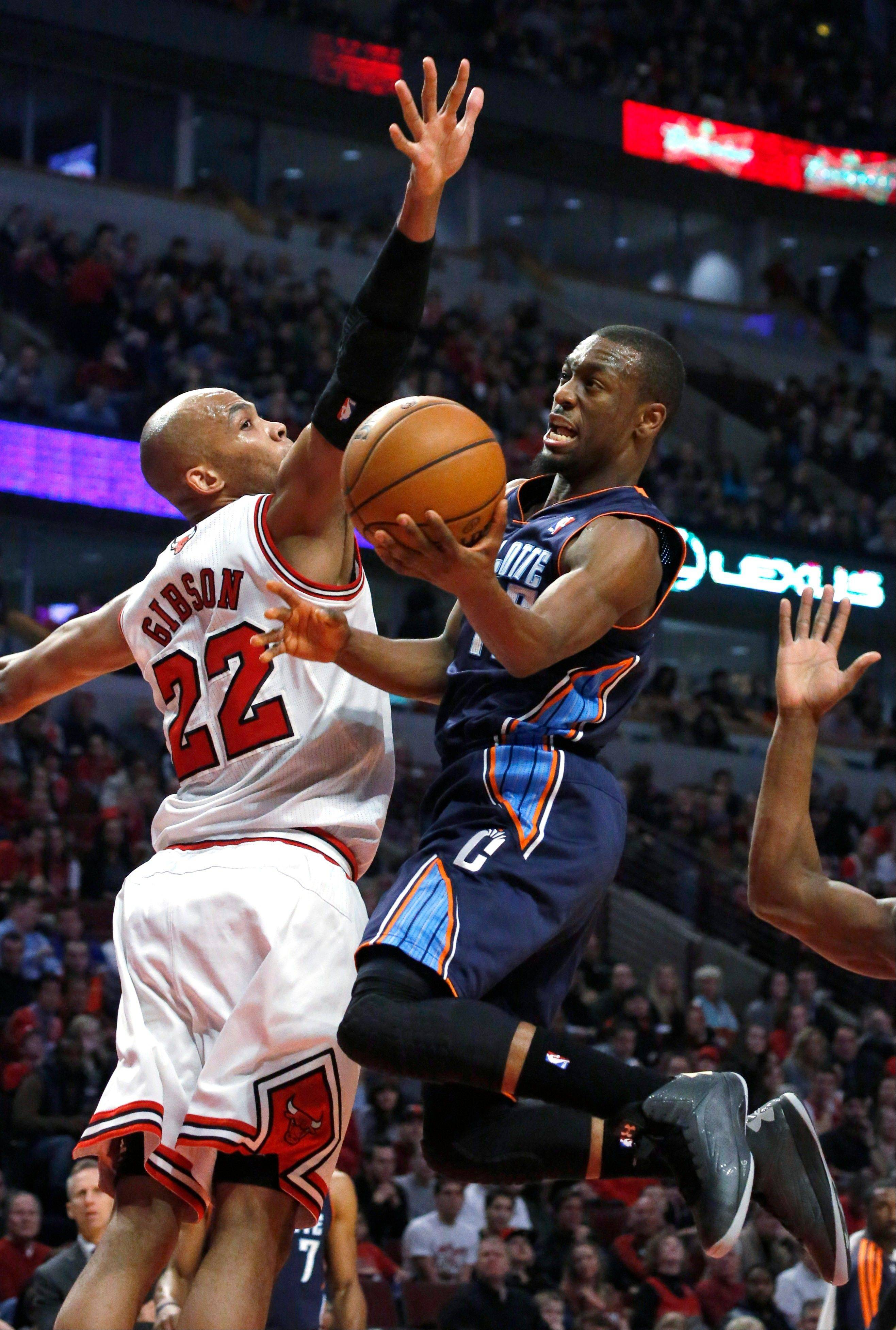 Charlotte Bobcats guard Kemba Walker (15) shoots past Chicago Bulls forward Taj Gibson (22) during the first half of an NBA basketball game Monday, Dec. 31, 2012, in Chicago.