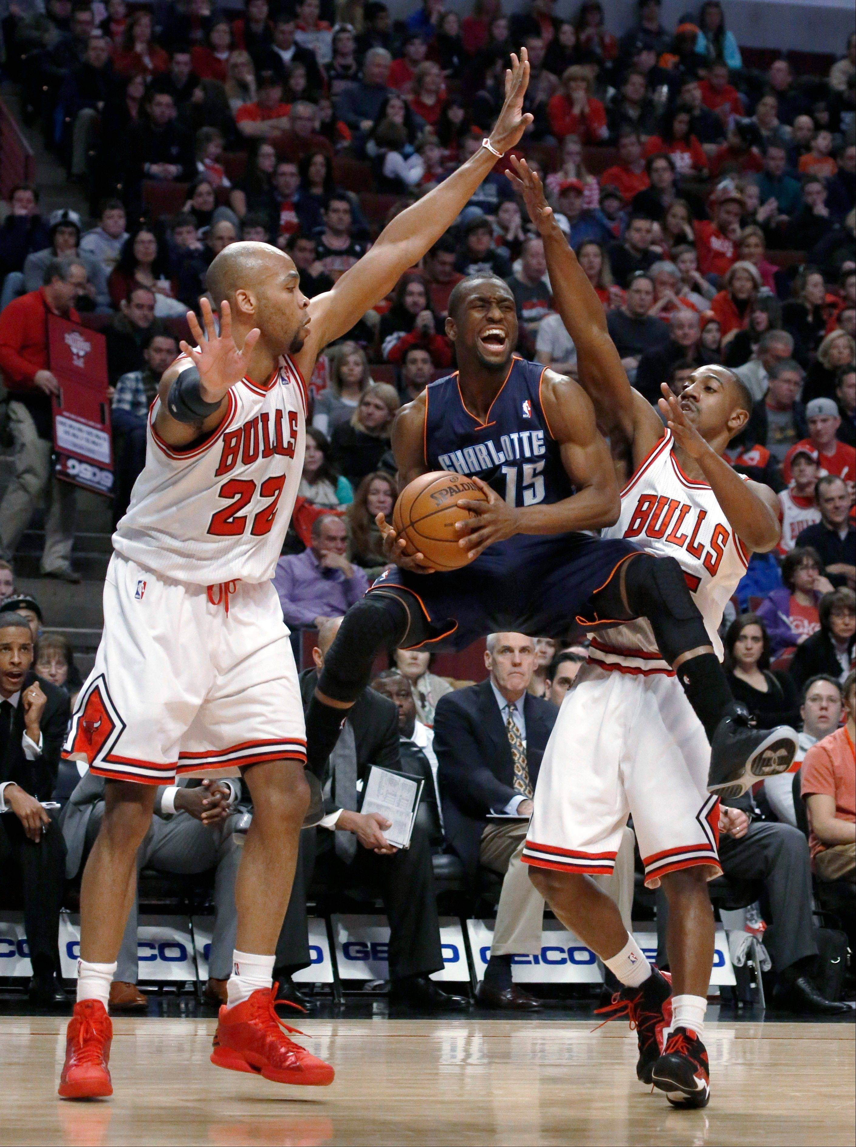 Charlotte Bobcats guard Kemba Walker (15) splits the defense of Chicago Bulls'Taj Gibson (22) and Marquis Teague during the first half of an NBA basketball game Monday, Dec. 31, 2012, in Chicago.