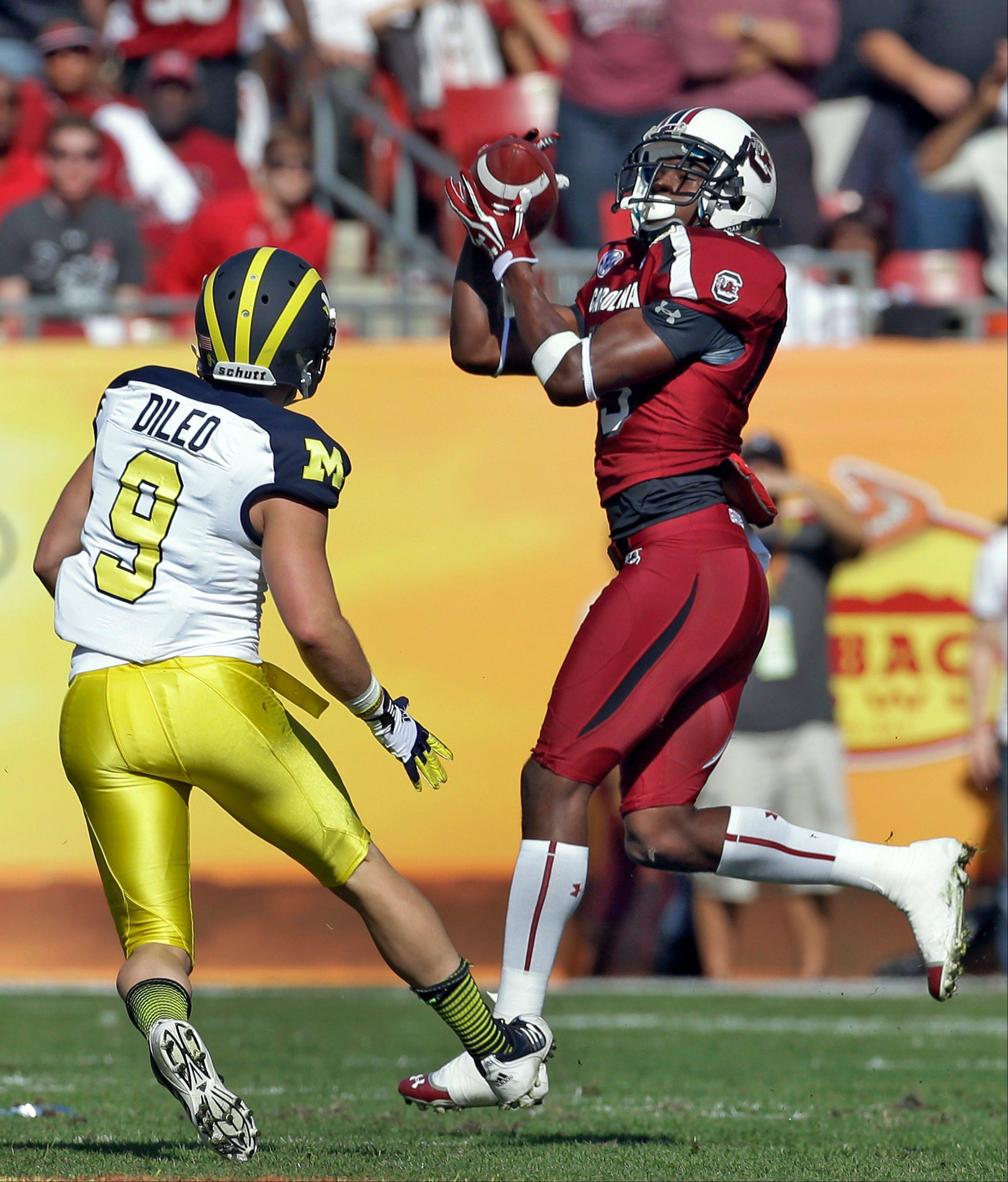 South Carolina cornerback Jimmy Legree (15) intercepts a pass intended for Michigan wide receiver Drew Dileo (9) during the first quarter of the Outback Bowl NCAA college football game, Tuesday, Jan. 1, 2013, in Tampa, Fla.
