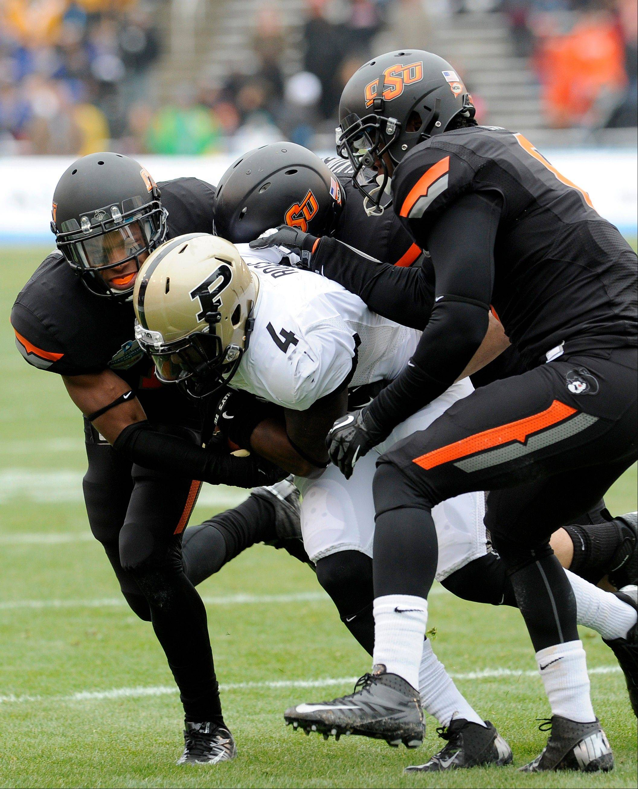 From left, Oklahoma State cornerback Kevin Peterson, linebacker Alex Elkins and safety Daytawion Lowe tackle Purdue wide receiver O.J. Ross (4) in the first half of the Heart of Dallas Bowl NCAA college football game, Tuesday, Jan. 1, 2013,in Dallas.