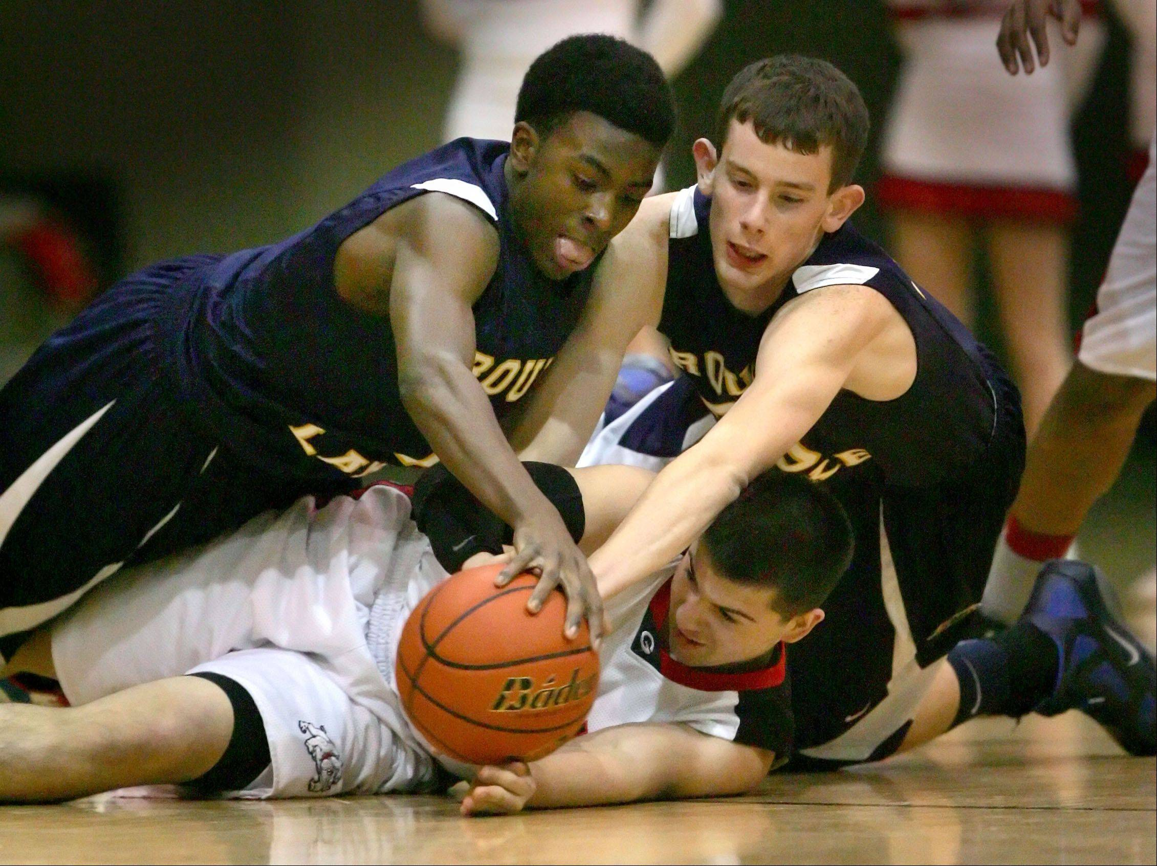 Round Lake�s Karnell Wright, left, and Zack Pick battle for a loose ball with Grant�s Luke Lostroscio during Wednesday�s game in Fox Lake.