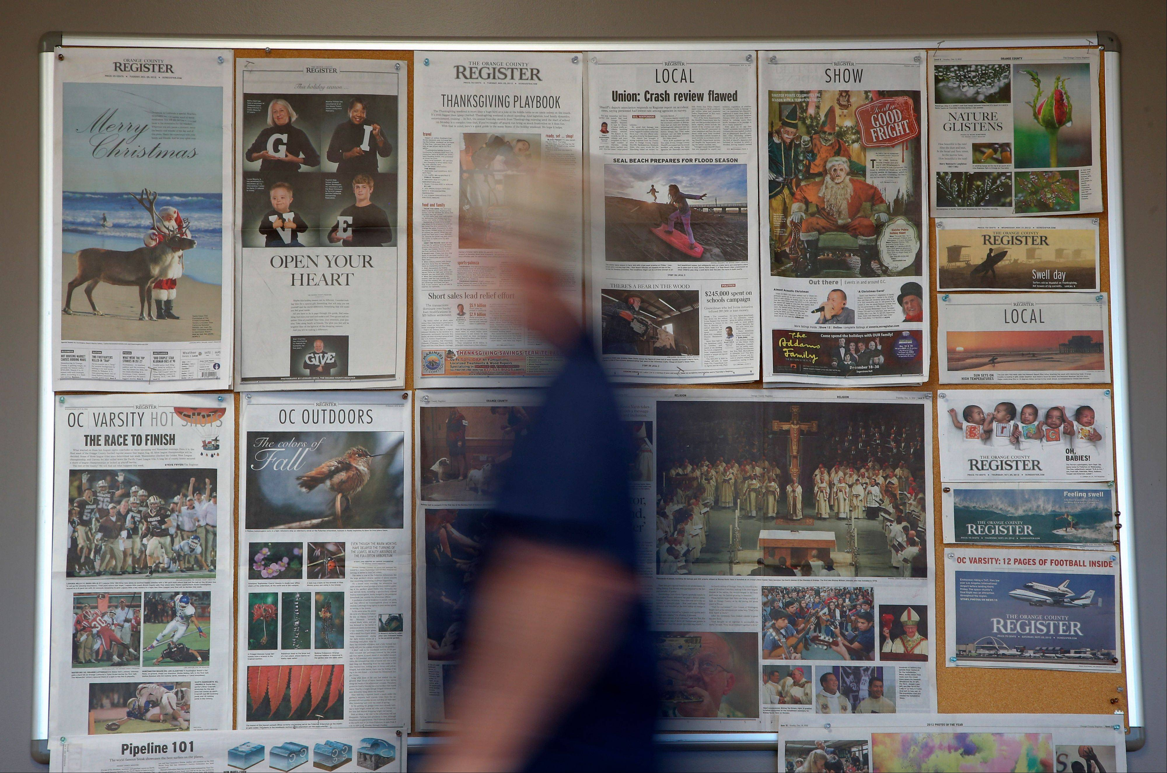 Some front pages and section fronts of the Orange County Register are seen in the newsroom in Santa Ana, Calif., Thursday.