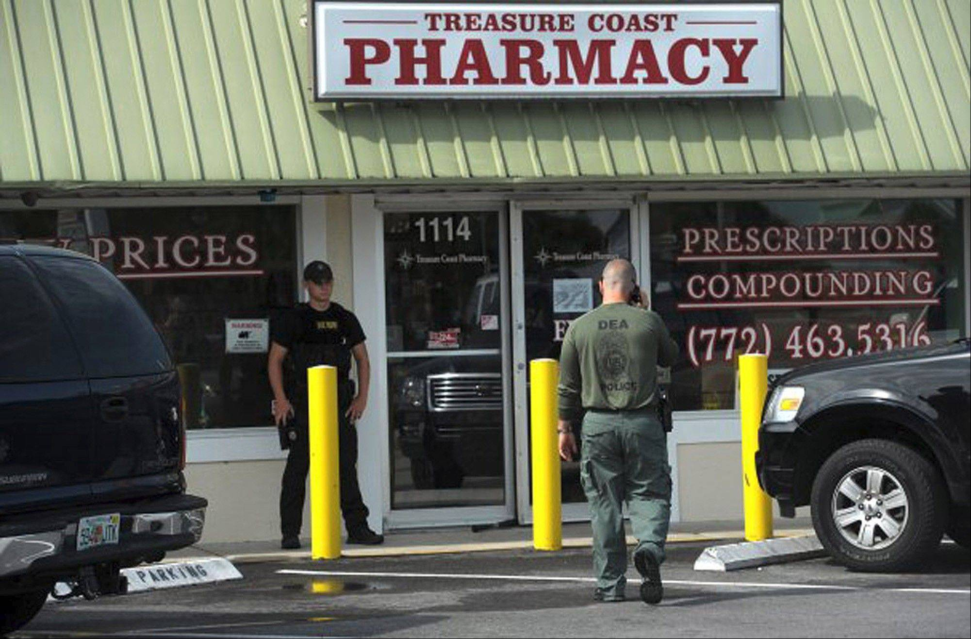 In this Tuesday, June 28, 2011 photo, agents with the Drug Enforcement Administration stand outside the Treasure Coast Pharmacy in Jensen Beach after a raid. shortly before it opened Tuesday morning as part of an ongoing investigation. DEA, the Florida Department of Health, Florida State Troopers, Martin County Sheriff's deputies and Boca Raton and Margate police participated in the investigation.