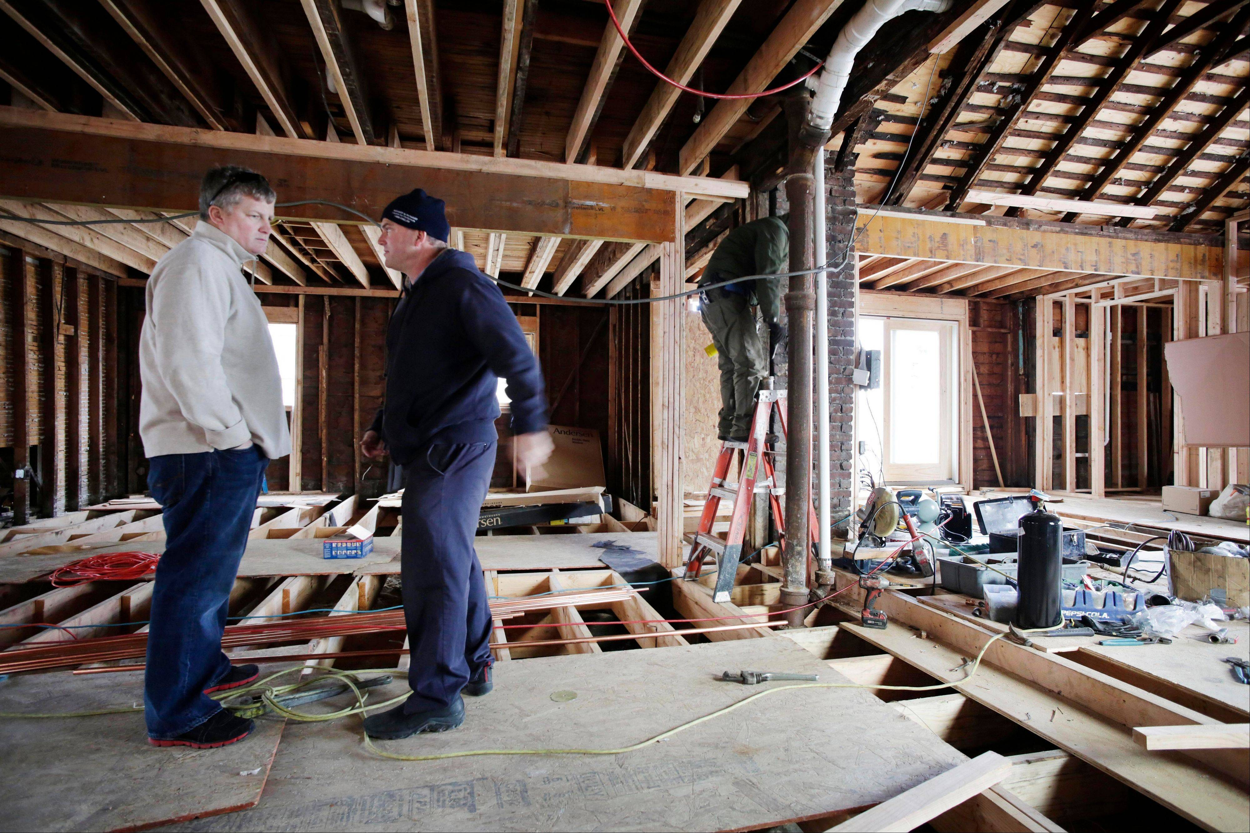 Joseph O'Grady, left, with Rockaway Reach, talks with Kevin Murphy as they discuss the renovation of Murphy's home in the Belle Harbor neighborhood of New York. Murphy's house was heavily damaged by flooding sea water during Superstorm Sandy on Oct. 29, 2012.