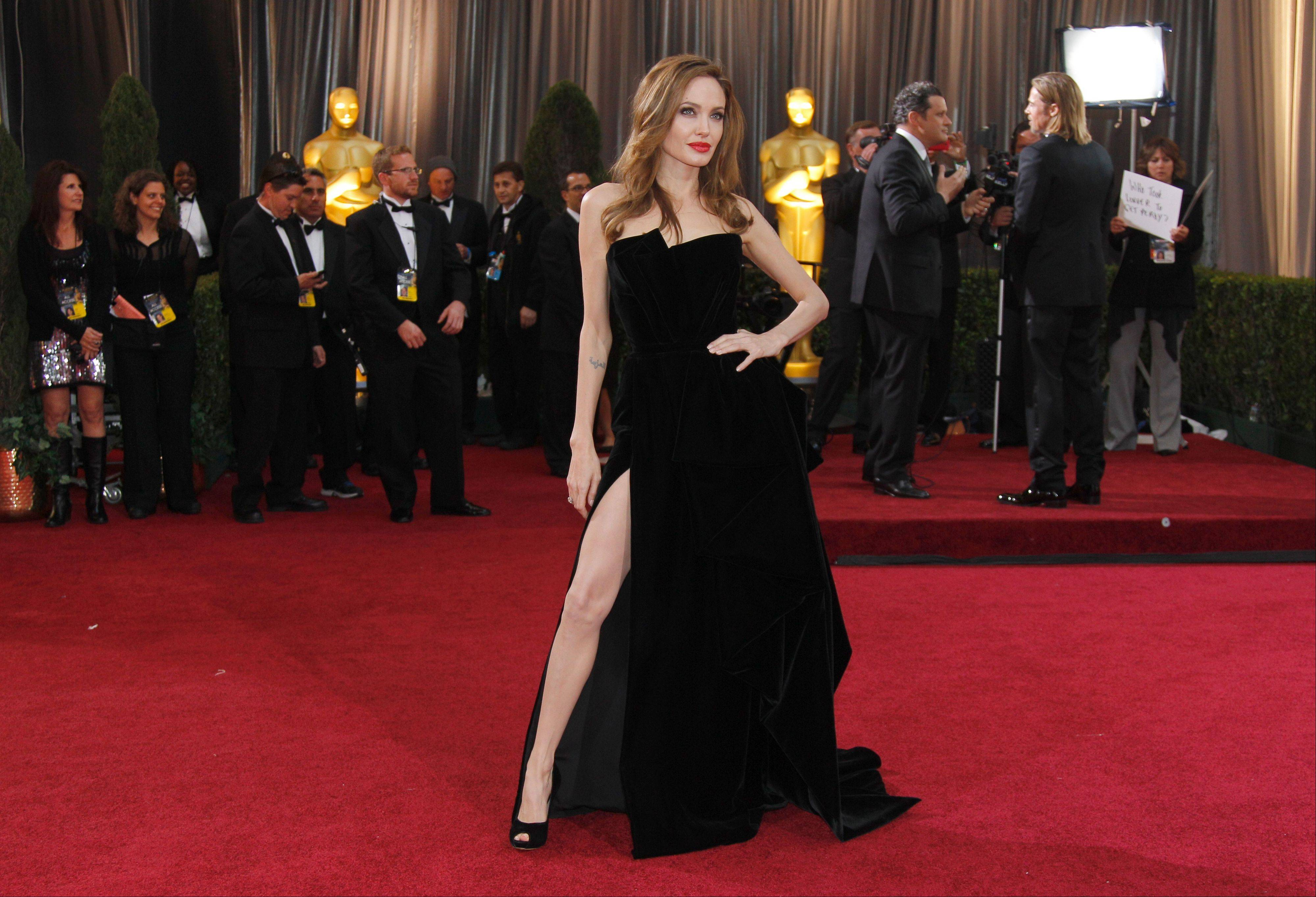 This Feb. 26, 2012 file photo shows Angelina Jolie posing before the 84th Academy Awards in the Hollywood section of Los Angeles. Every year fashion offers up the good, the bad and the ugly. But what the industry is really built on _ and consumers respond to _ is buzz. Jolie's leg, that peeked out of the high thigh-high slit of her Versace gown, was the most exciting appearance on the red carpet.