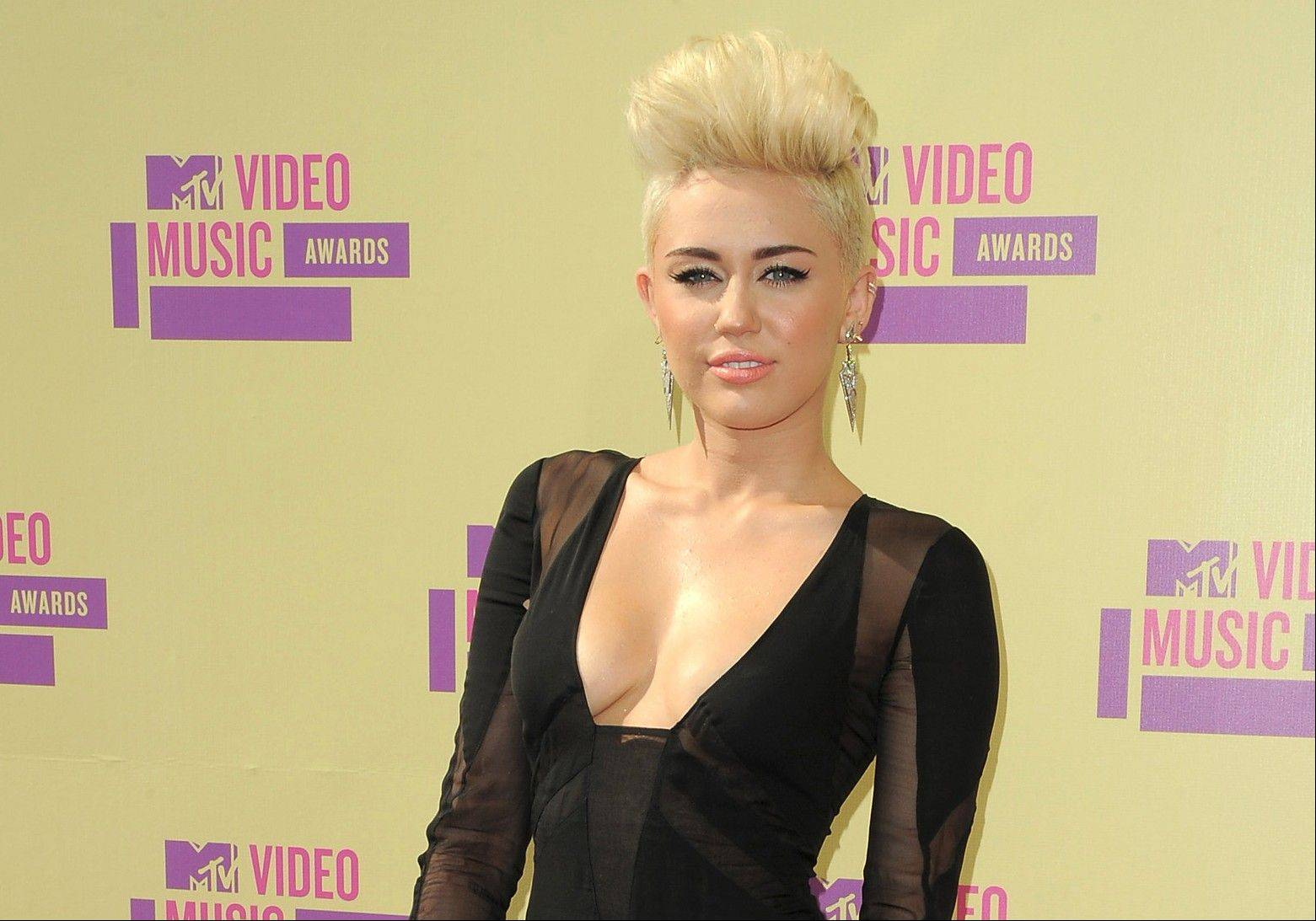 In this Sept. 6, 2012 file photo, Miley Cyrus attends the MTV Video Music Awards in Los Angeles. When Cyrus cut off the long hair her fans had become used to, she took some heat. She has said (and tweeted) repeatedly, though, that she was pleased with the new punk-pixie look and was sticking with it.