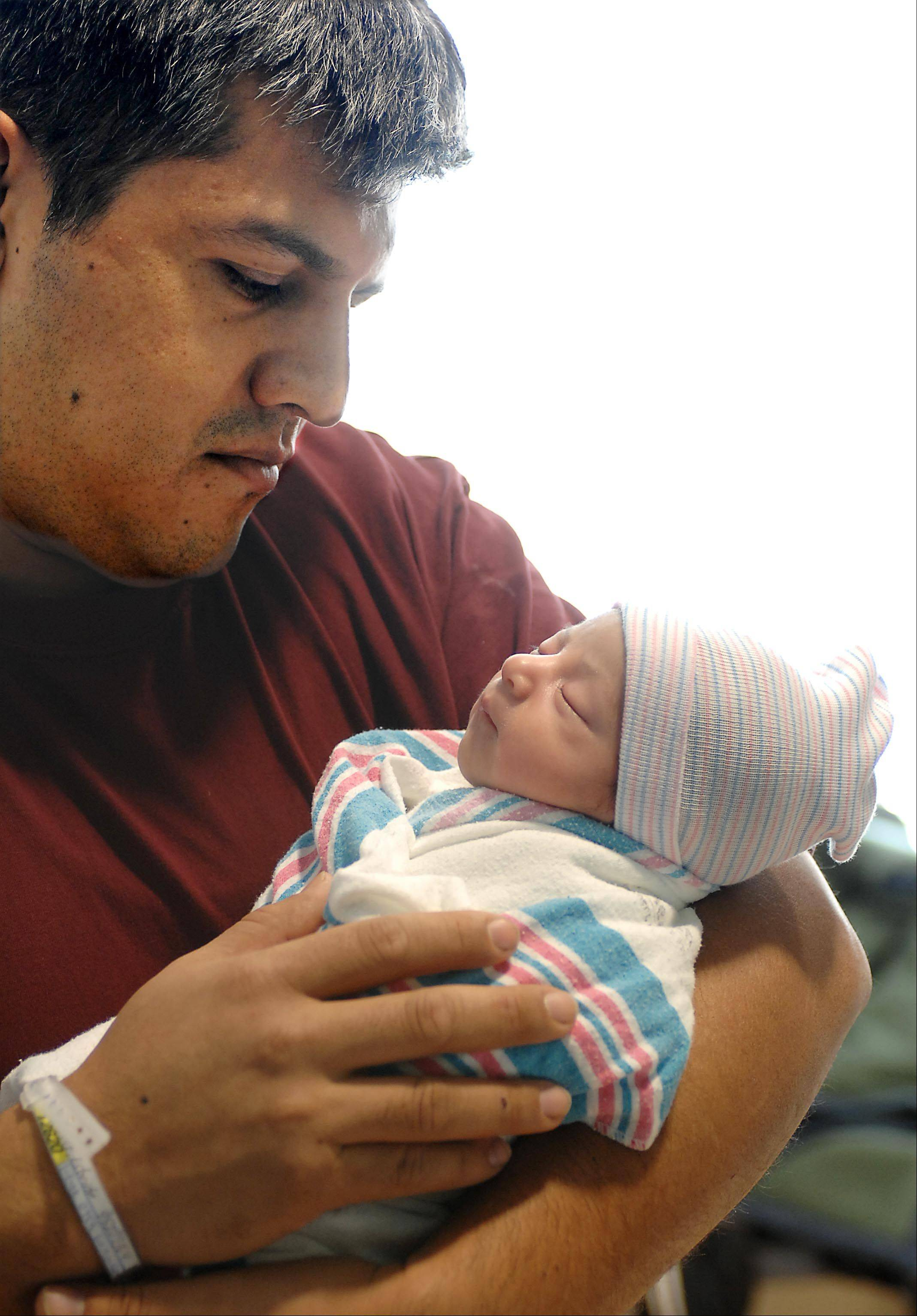 Daniel Hernandez of Algonquin holds his daughter Isabel, the first baby born in Kane County in 2013. He's had some practice: Isabel has three sisters and one brother. She was born at 8:43 a.m. Jan. 1 at Sherman Hospital in Elgin.
