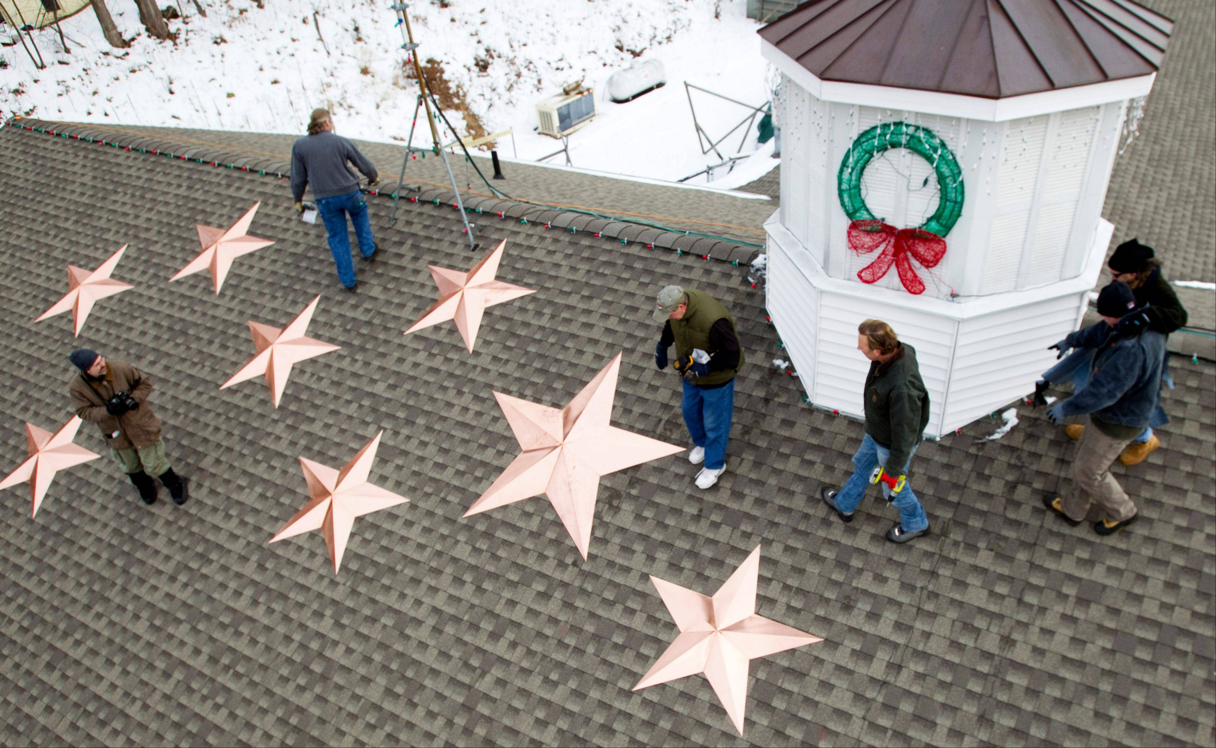 People work on the installation of 26 stars on the roof of the Sandy Hook fire station Tuesday in Newtown, Conn. The stars were made and installed by a group of local contractors, led by Greg Gnandt, to honor the memory of the victims of the Sandy Hook school shooting.