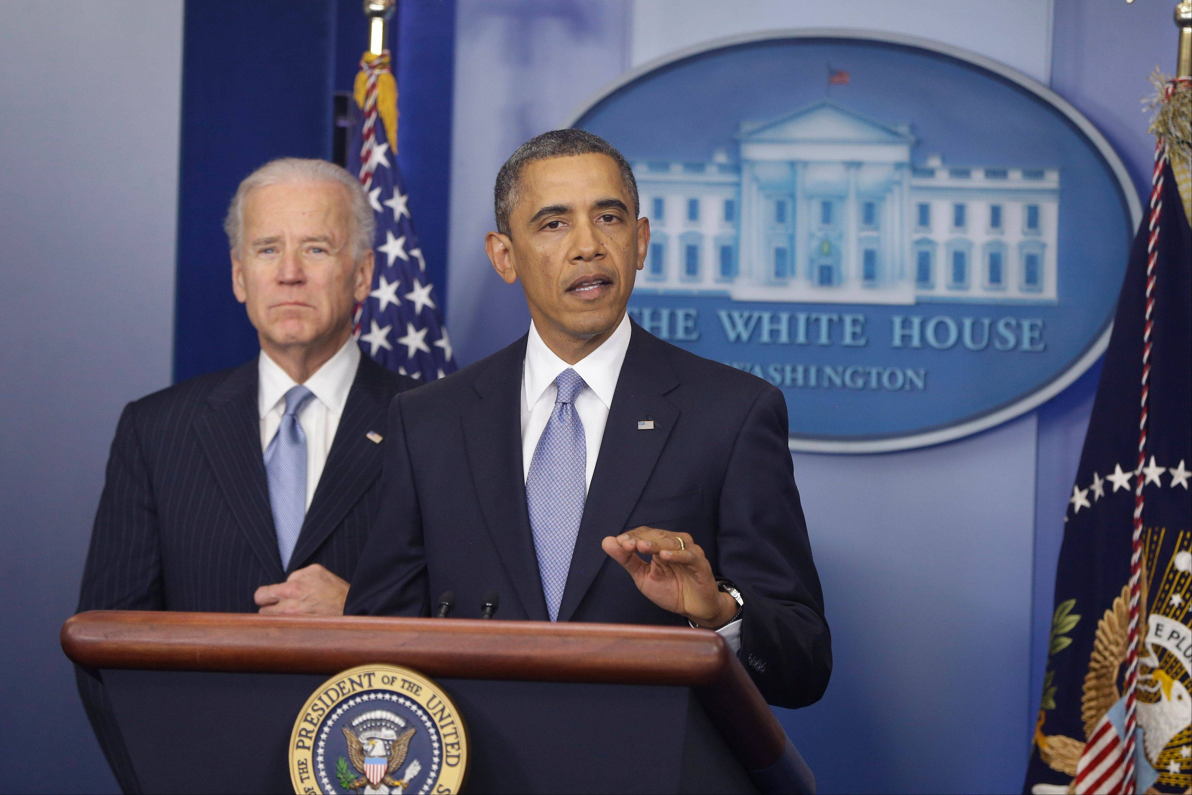 President Barack Obama, with Vice President Joe Biden looking on, makes a statement regarding passage of the fiscal cliff bill at the White House Tuesday evening.