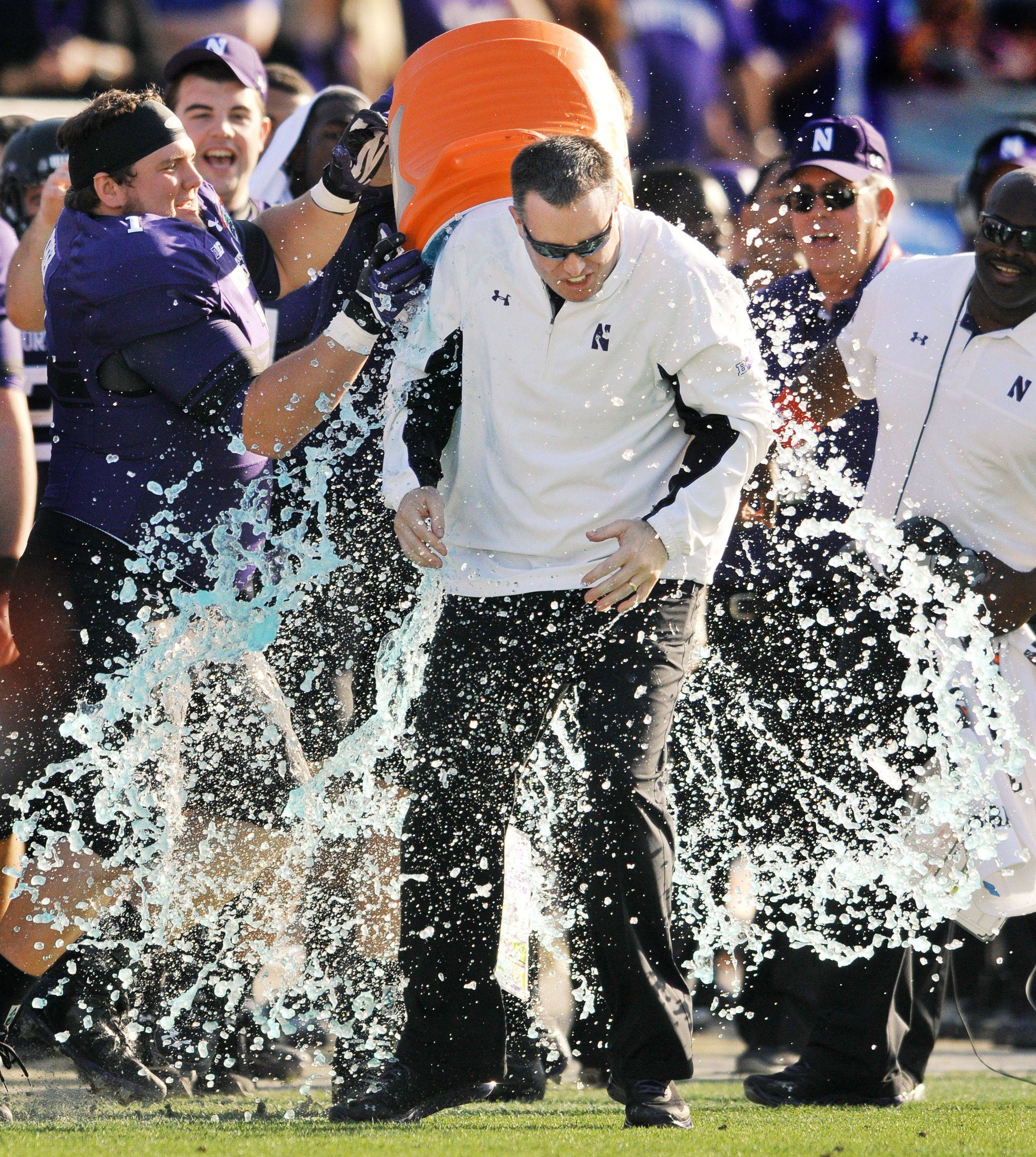 Northwestern coach Pat Fitzgerald is doused in the closing minute of the Wildcats' Gator Bowl victory over Mississippi State, the first bowl win for NU in 64 years.