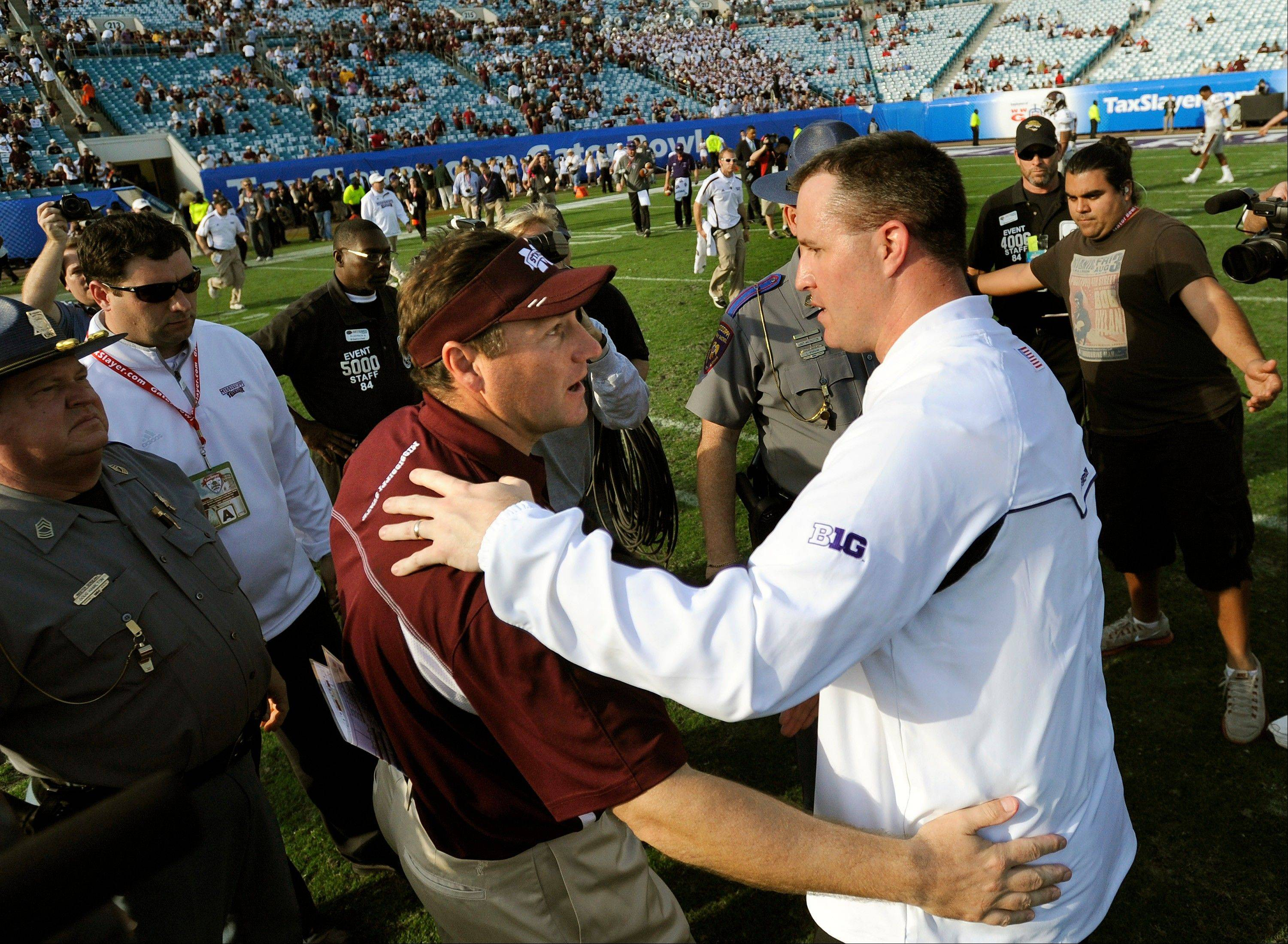Northwestern head coach Pat Fitzgerald, right, and Mississippi State head coach Dan Mullen, left, greet each other after the Gator Bowl NCAA college football game, Tuesday, Jan. 1, 2013 in Jacksonville, Fla. Northwestern won 34-20.