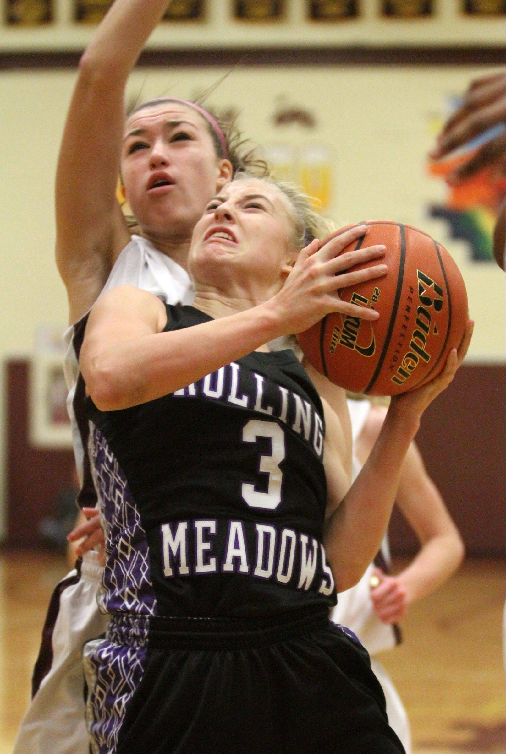 Rolling Meadows' Jackie Kemph looks to shoot past Montini defender Kelsey Bogdan, left, in championship game of Montini holiday tournament in Lombard on Saturday.