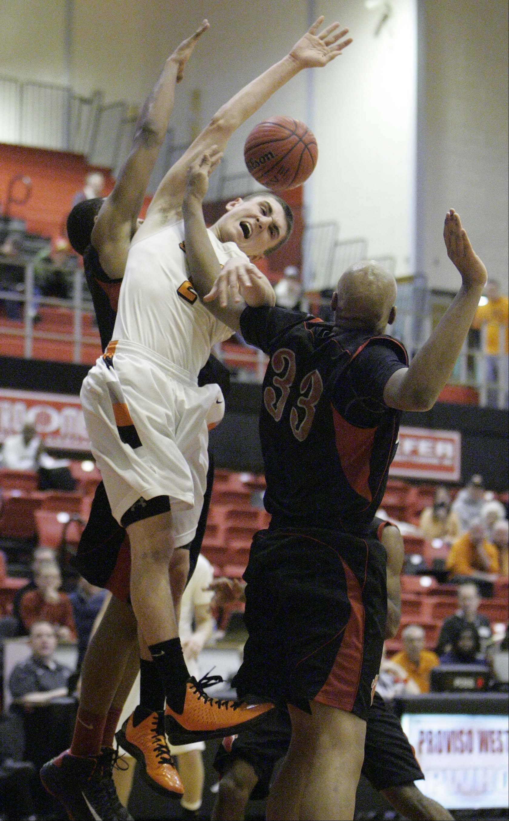 St. Charles East's Dom Adduci, 2, goes to the hoop past Von Steuben's Malachi Matias, 33, at the Proviso West Holiday Tournament in Hillside on Wednesday.
