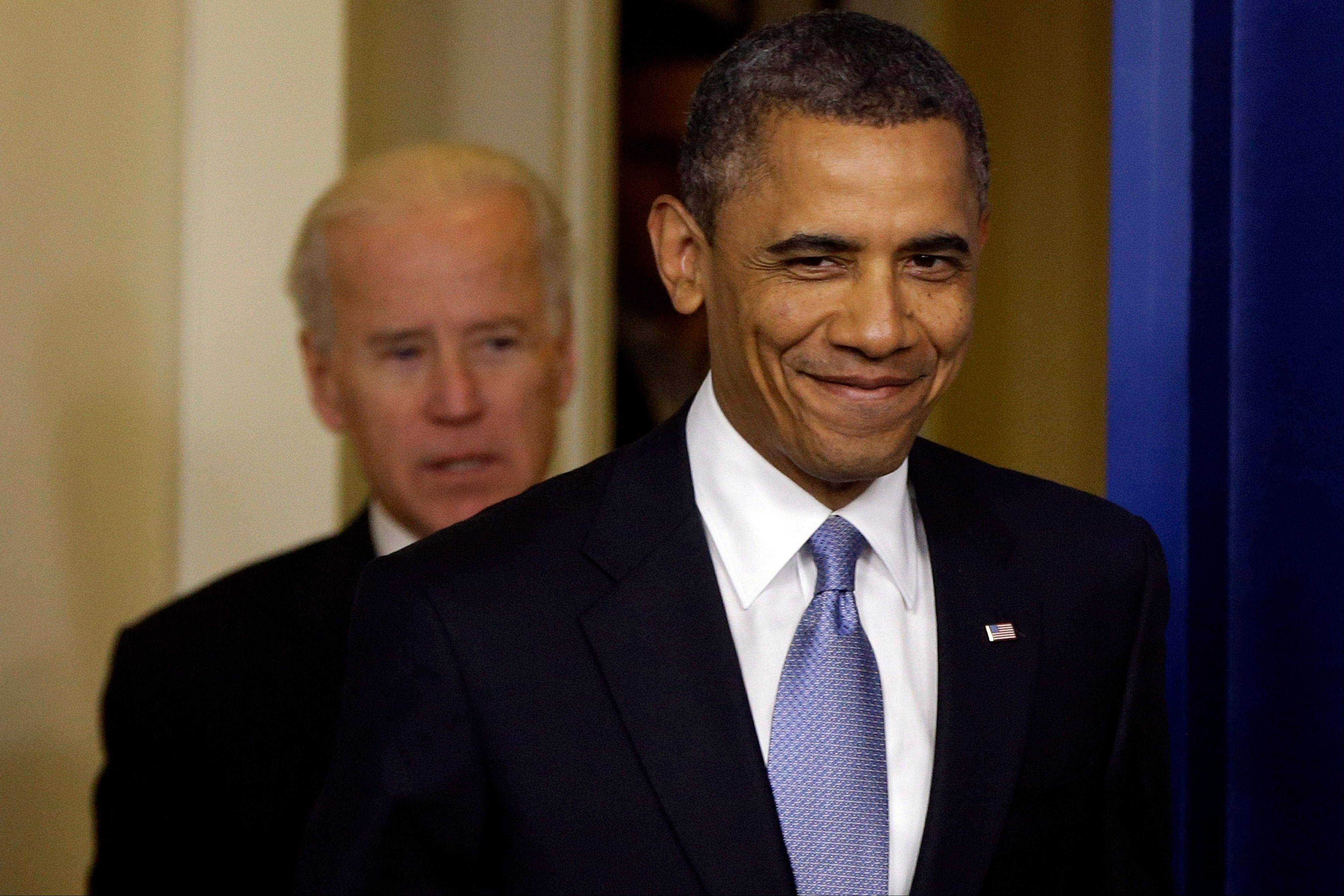 President Barack Obama smiles Tuesday as he arrives with Vice President Joe Biden to make a statement regarding the passage of the fiscal cliff bill in the Brady Press Briefing Room at the White House in Washington.