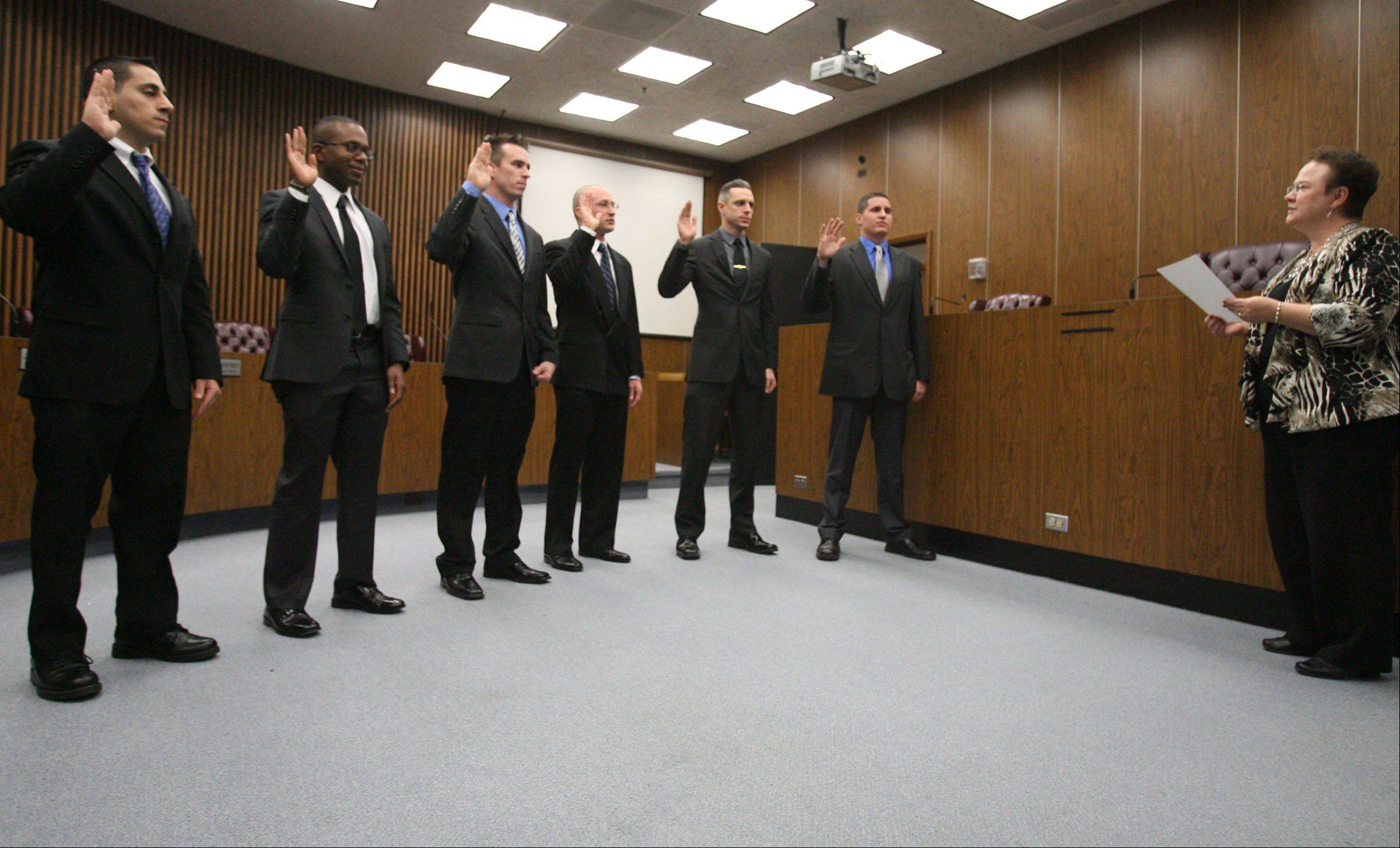 Police officers Jack Azar, left to right, William Cozzens, Jimmy Armstrong, Carl Faust, Curtis Miller and Thomas Doig were sworn in Wednesday by Des Plaines City Clerk Gloria Ludwig in the city council chambers at Des Plaines City Hall.