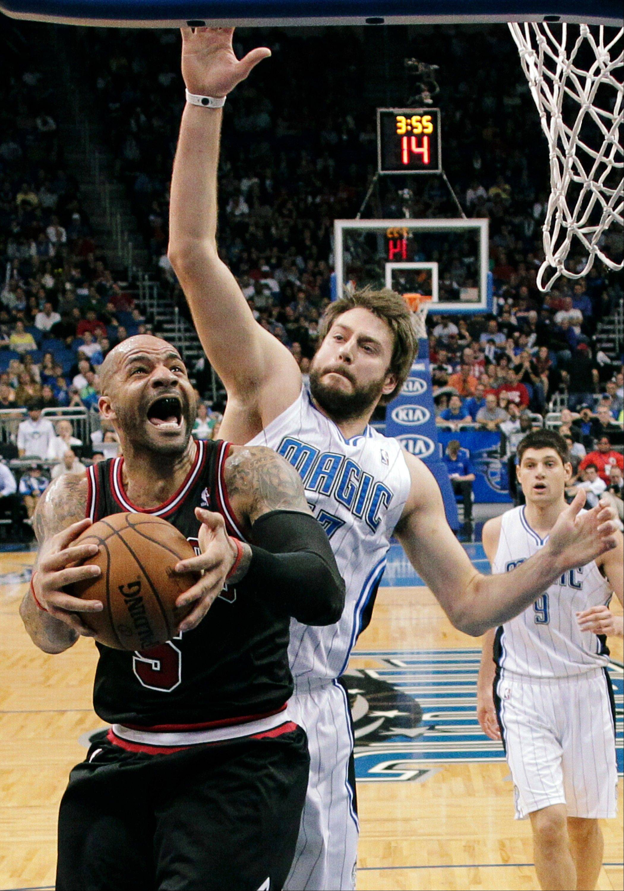 The Bulls� Carlos Boozer, who finished with a season-high 31 points, goes to the basket in front of Orlando�s Josh McRoberts.