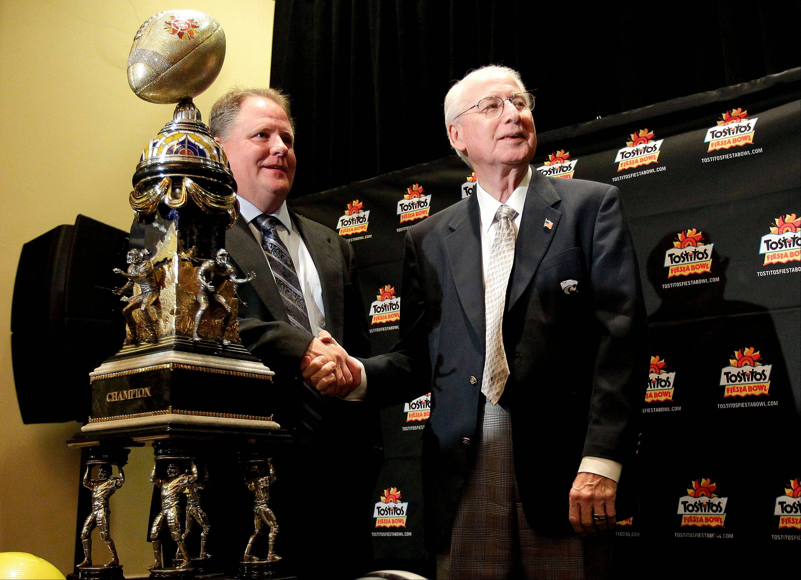 Oregon head coach Chip Kelly, left, and Kansas State head coach Bill Snyder pose Wednesday with the Fiesta Bowl champions trophy in Scottsdale, Ariz. Oregon and Kansas state play Thursday in the Fiesta Bowl.