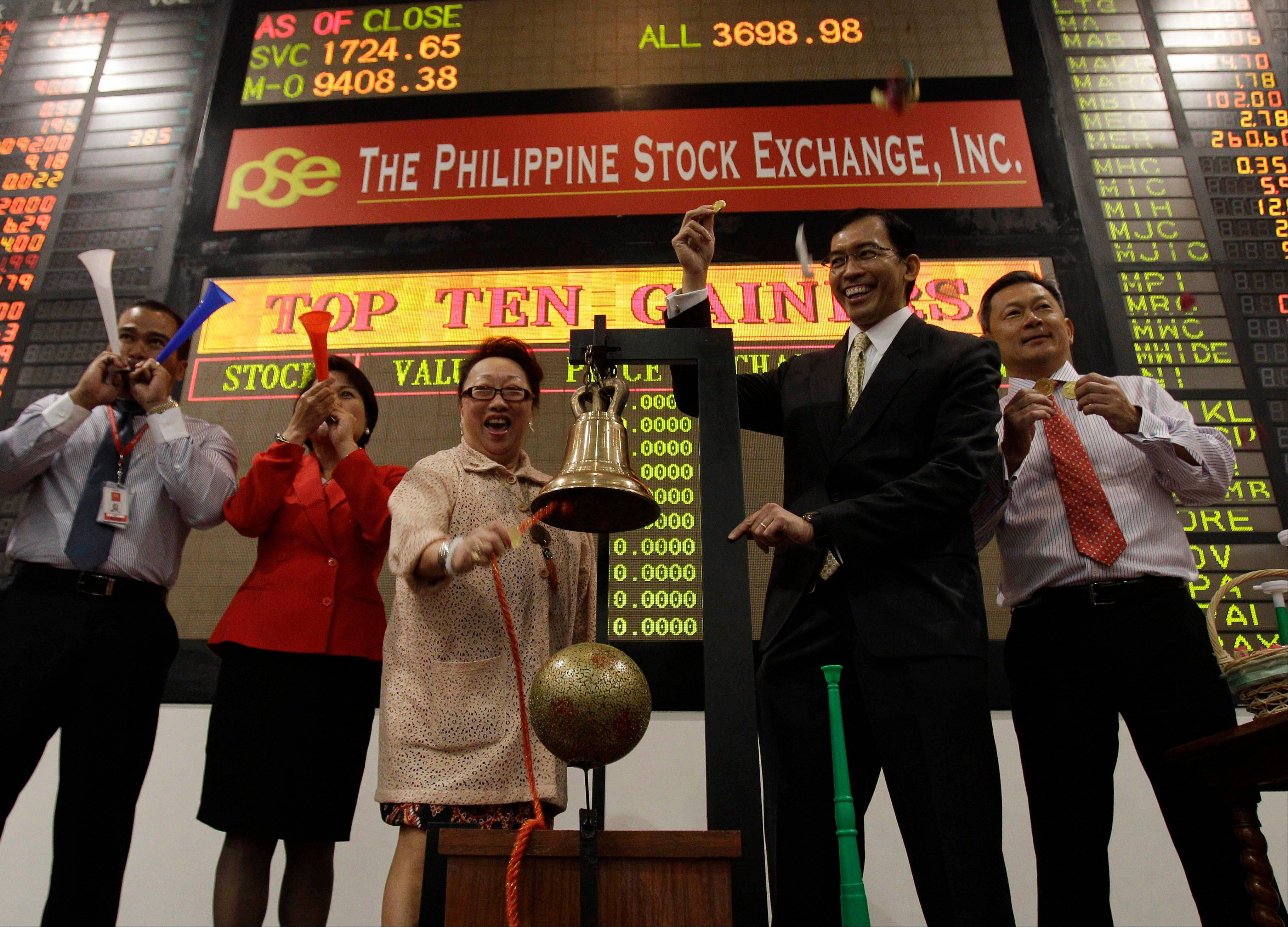 Philippine Stock Exchange President and CEO Hans Sicat, second from right, gestures as PSE treasurer Ma. Vivian Yuchengco rings the bell to signal the start of the first day of trading at Philippine Stock Exchange at the financial district of Makati, south of Manila, Philippines on Wednesday Jan. 2.