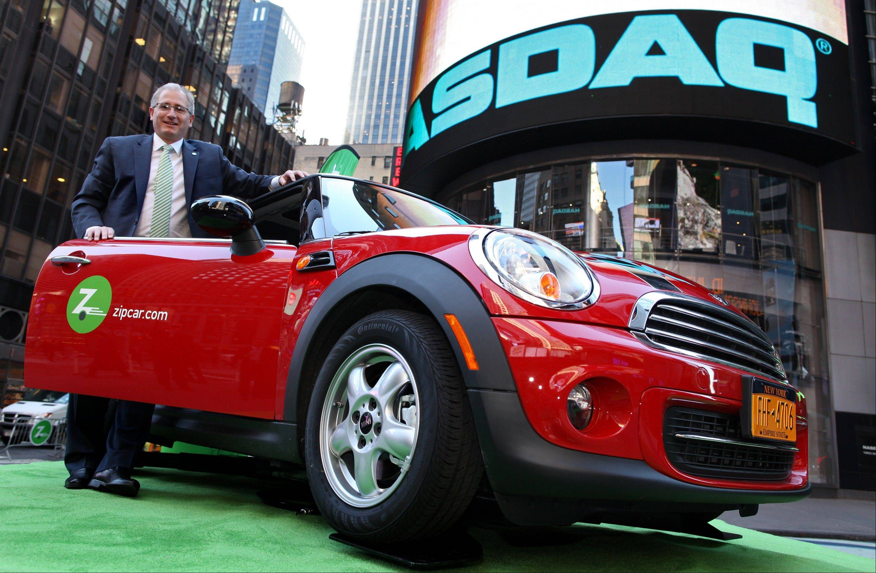 In this April 14, 2011 photo Zipcar Chairman and CEO Scott Griffith stands with a Zipcar Mini-Cooper before the opening bell at the NASDAQ Market Site in New York.
