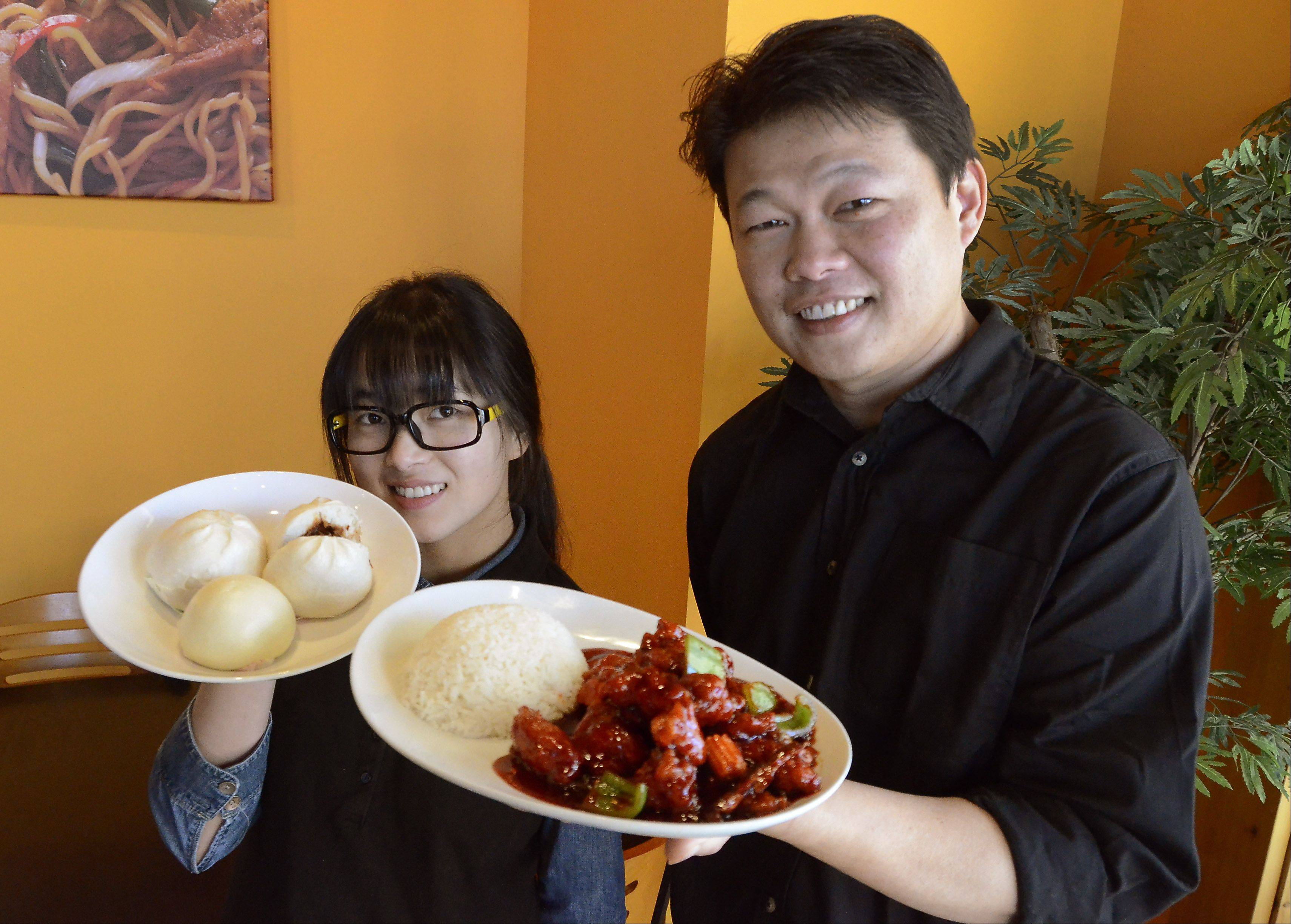 Server Jiang Zhao and co-owner Alex Liang show off the specialties of the house at Bao Gourmet in Bartlett.