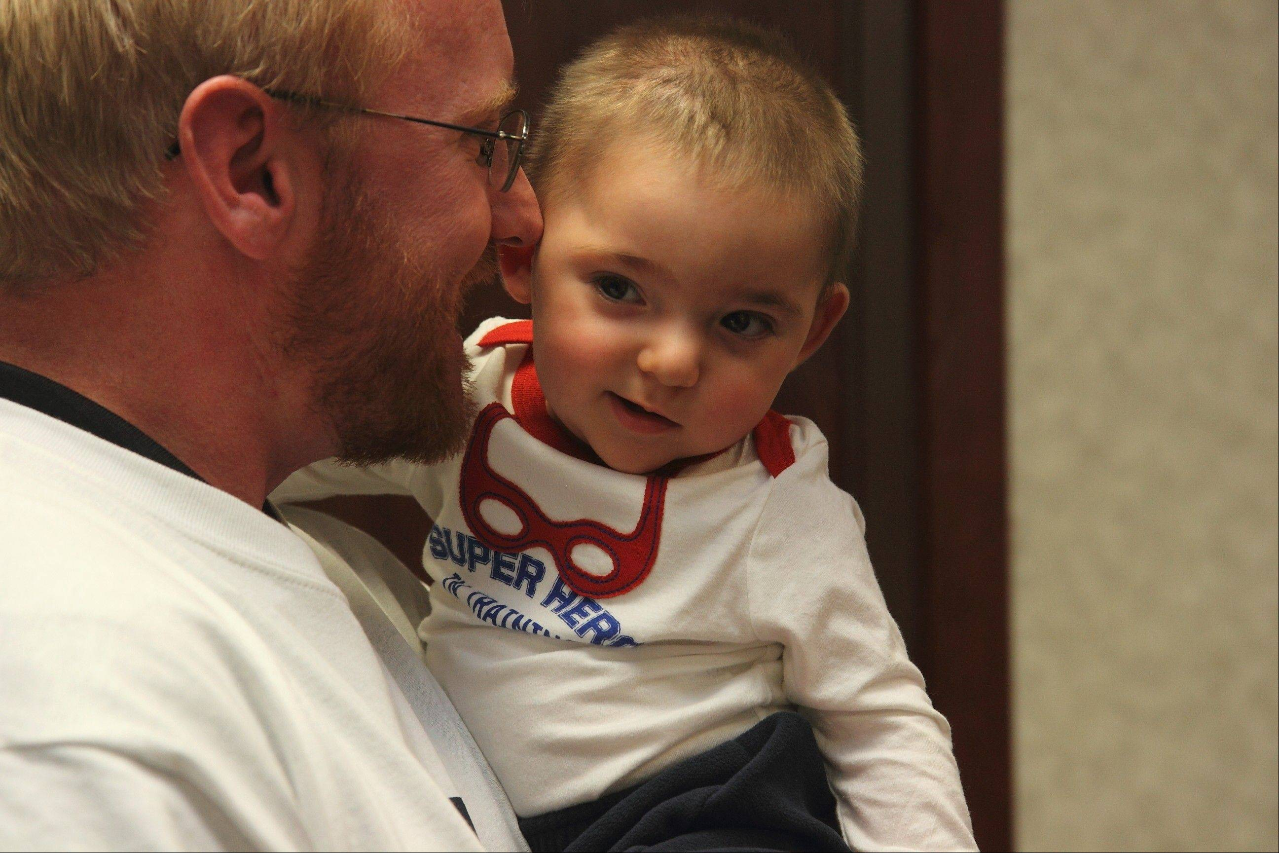 Matthew Erickson, a Huntley boy who was born with brain cancer, recently celebrated his first birthday with a superhero themed birthday party that attracted nearly 200 people on Dec. 9. Here he is with his father, Ben.