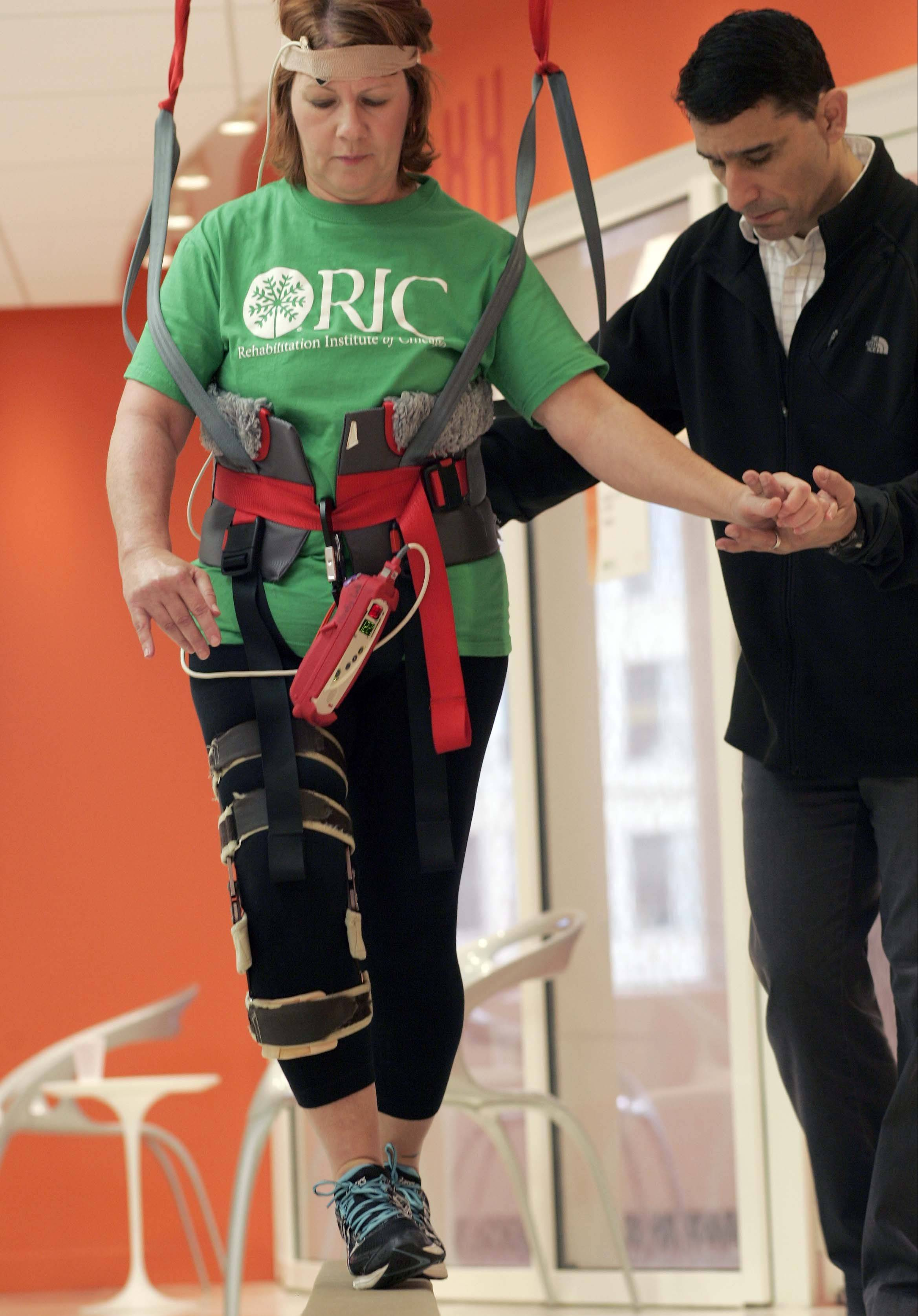 Kathy Pacholski of Chicago traverses a balance beam with Research Scientist and Physical Therapist T. George Hornby close by her side at the Rehabilitation Institute of Chicago. U.S. Sen. Mark Kirk and Pacholski, who both participated in an experimental walking trial at the Institute, credit the therapy sessions with helping their recovery.