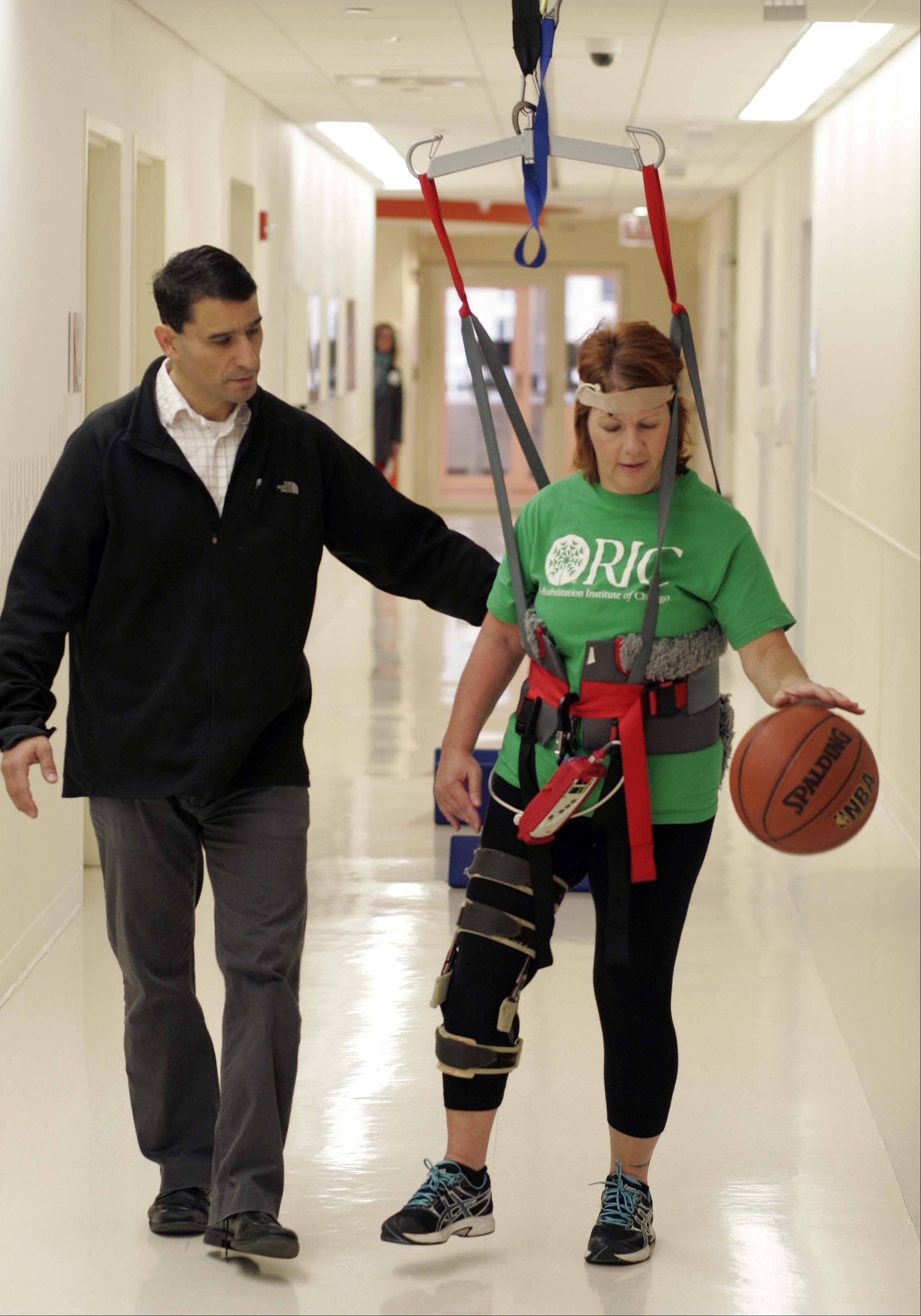Kathy Pacholski dribbles and walks quickly as she works with Research Scientist and Physical Therapist T. George Hornby at the Rehabilitation Institute of Chicago. The exercises are part of an experimental walking training regimen for stroke patients, completed by both Pacholski and U.S. Sen. Mark Kirk.