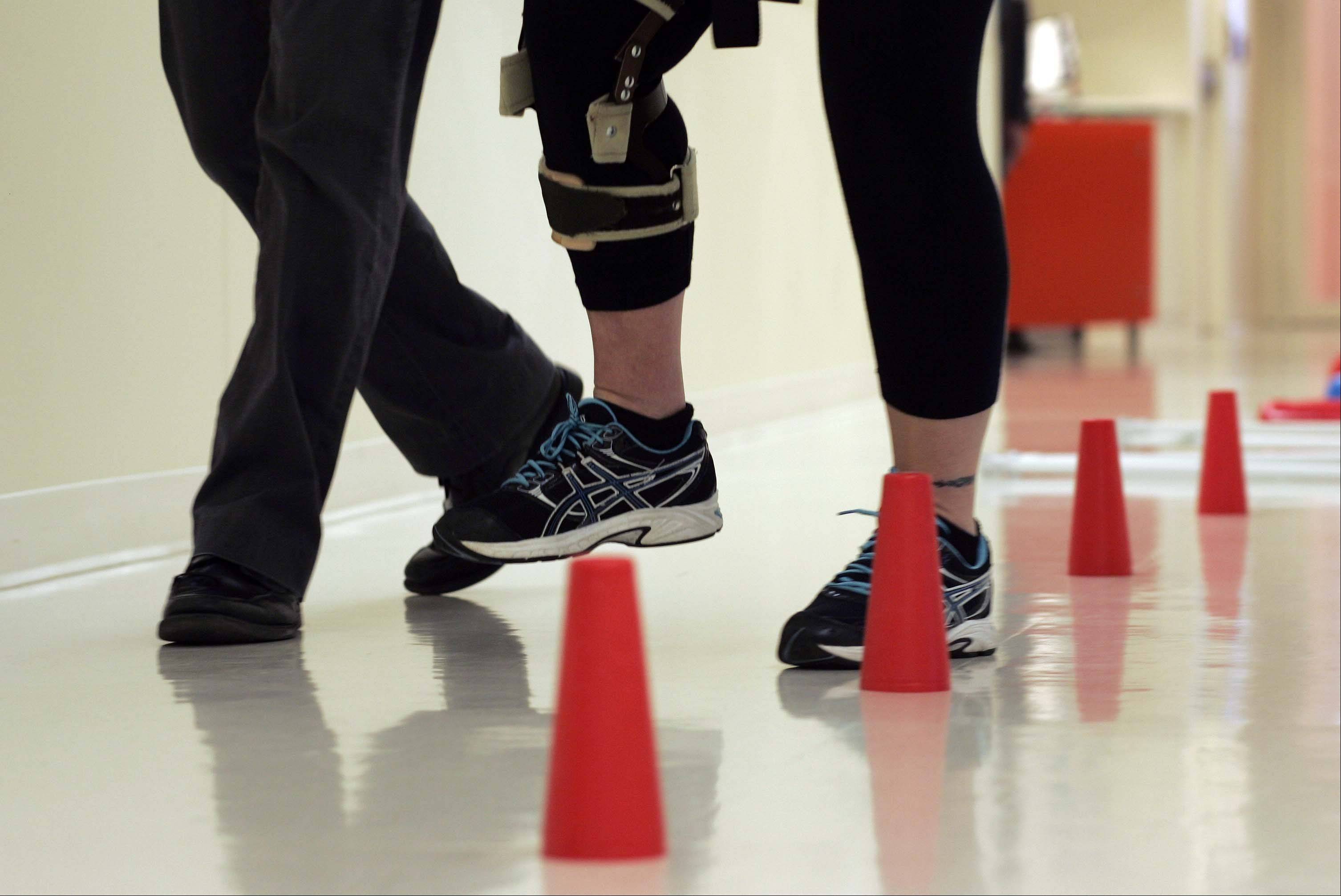 Kathy Pacholski moves her feet quickly and deliberately around cones while she works with Research Scientist and Physical Therapist T. George Hornby at The Rehabilitation Institute of Chicago. Senator Kirk would have done much of the same rehabilitation exercises that Pacholski has finished.