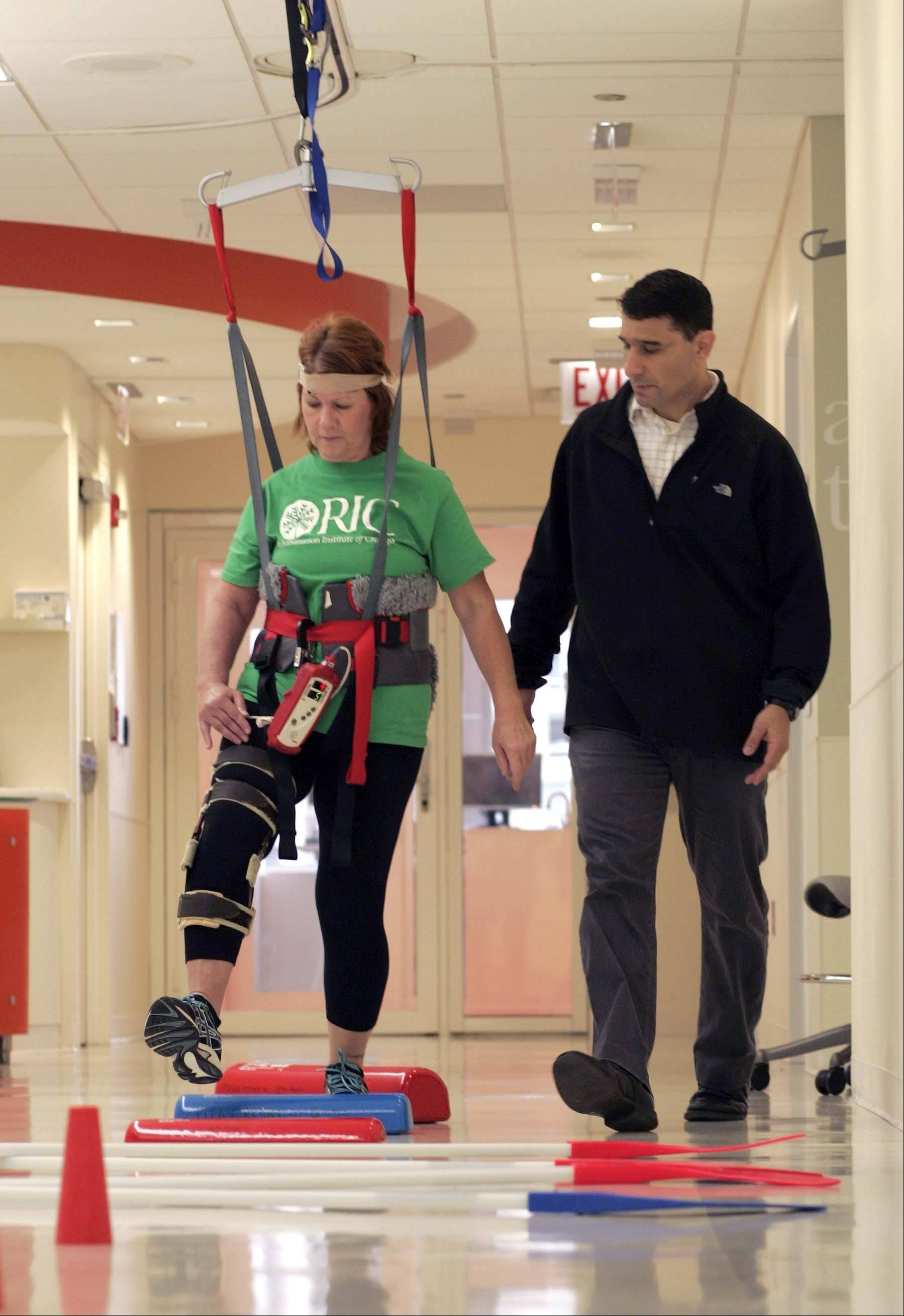 Kathy Pacholski works with Research Scientist and Physical Therapist T. George Hornby at the Rehabilitation Institute of Chicago, where she participated in a walking trial for stroke victims. Patients often wear a harness and a heart monitor while performing exercises.