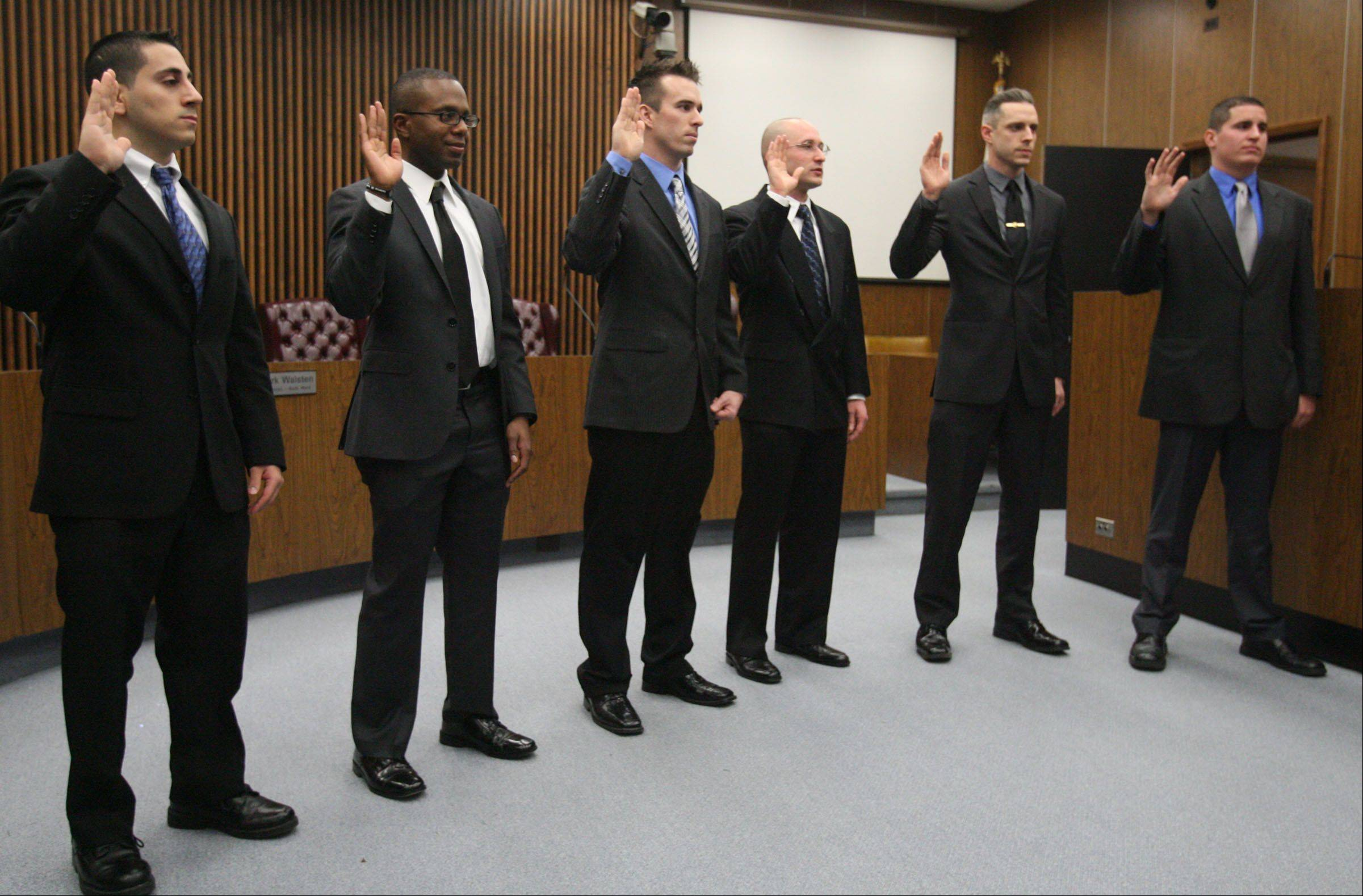 Police officers Jack Azar, left to right, William Cozzens, Jimmy Armstrong, Carl Faust, Curtis Miller, and Thomas Doig were sworn in Wednesday by Des Plaines City Clerk Gloria Ludwig in the city council chambers at Des Plaines City Hall.