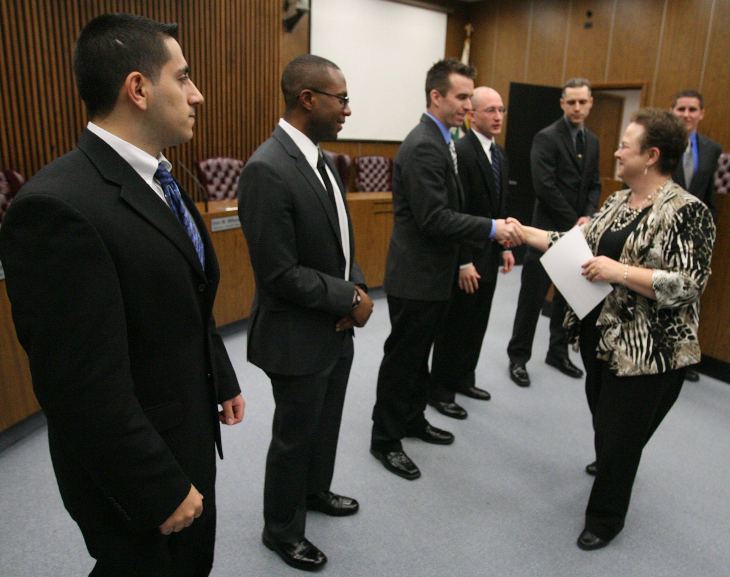 Des Plaines City Clerk Gloria Ludwig congratulated police officers Jack Azar, left to right, William Cozzens, Jimmy Armstrong, Carl Faust, Curtis Miller, and Thomas Doig after swearing them in Wednesday at Des Plaines City Hall.