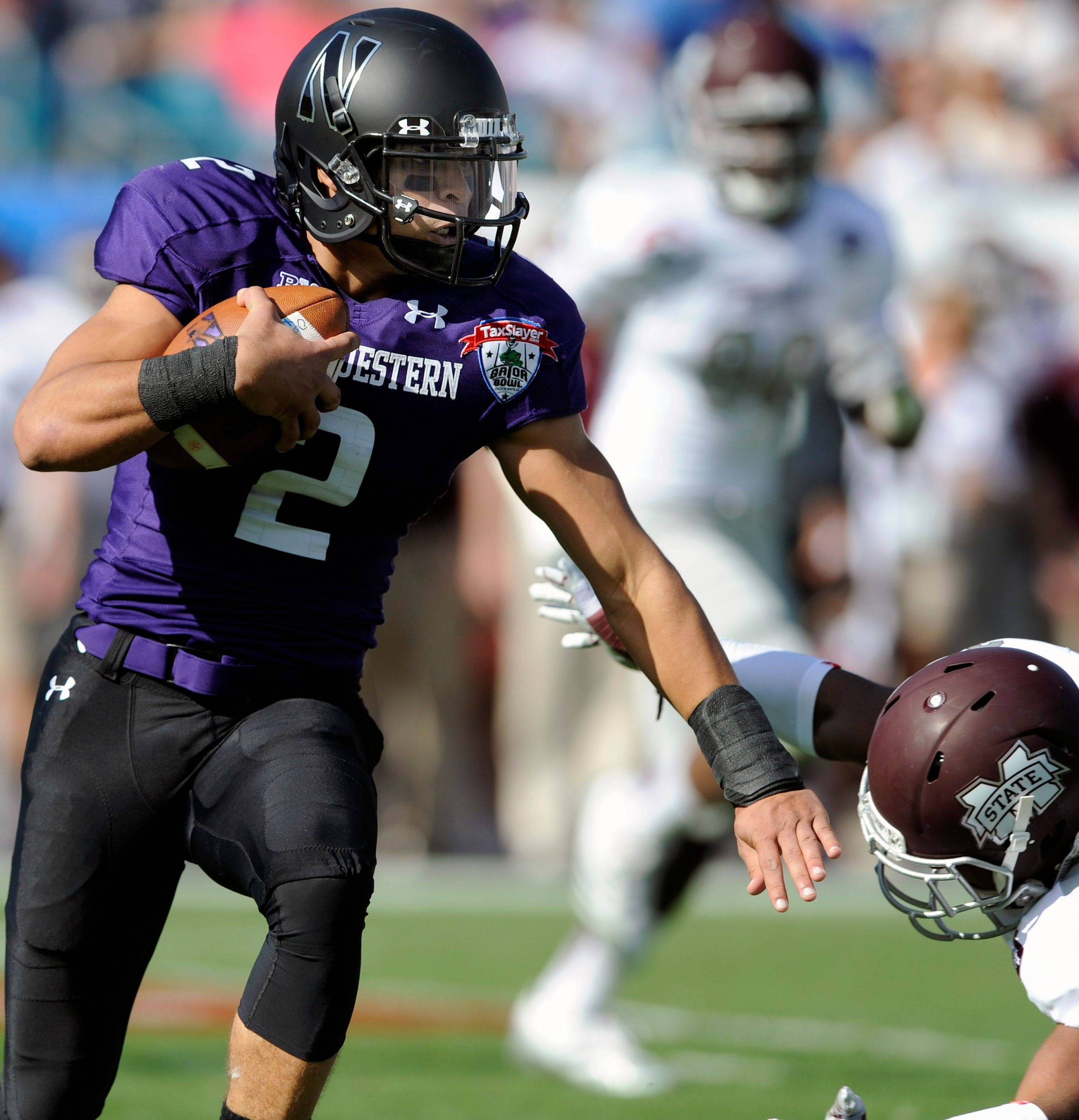 Northwestern quarterback Kain Colter stiff arms Mississippi State defensive back Jay Hughes during the first half of the Gator Bowl on Tuesday. Colter ran for 71 yards on 11 attempts in the Wildcats' victory.