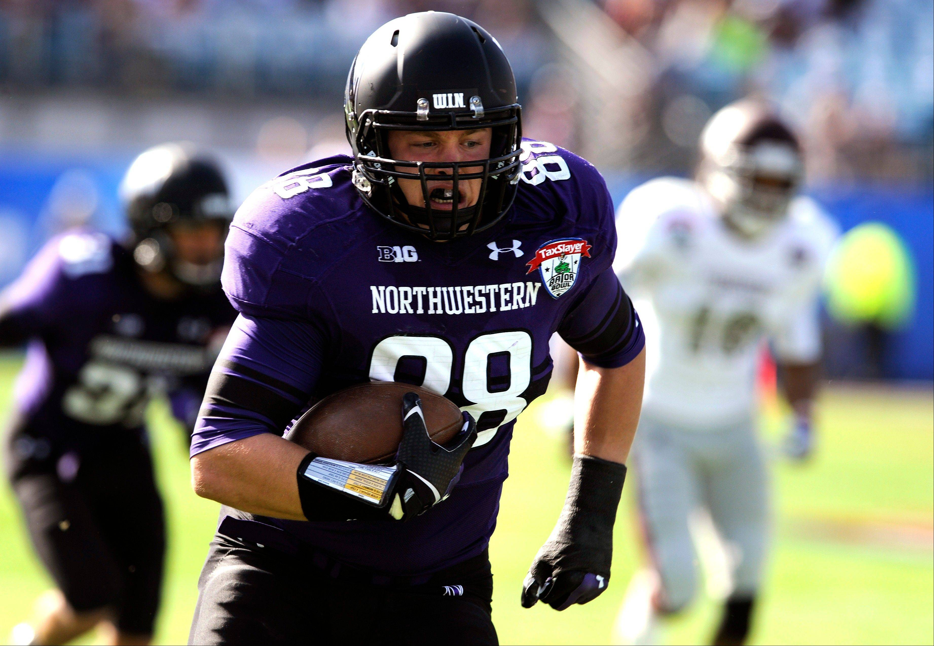 Northwestern defensive lineman Quentin Williams (88) returns an interception for a touchdown during the first half of the Gator Bowl NCAA college football game against Mississippi State Tuesday in Jacksonville, Fla.