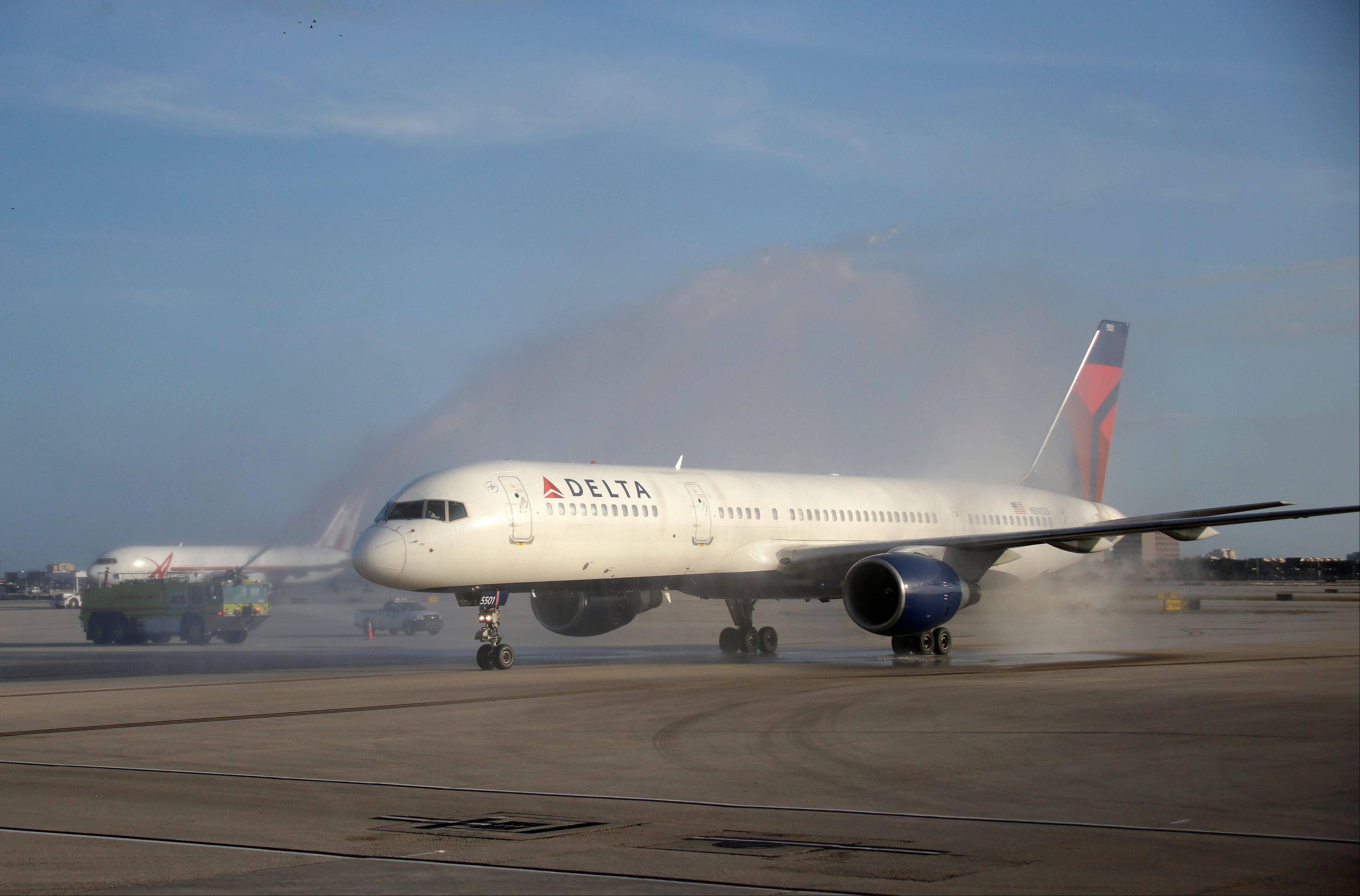 An airplane carrying the Alabama team is sprayed with a water cannon Wednesday after arriving at Miami International Airport.